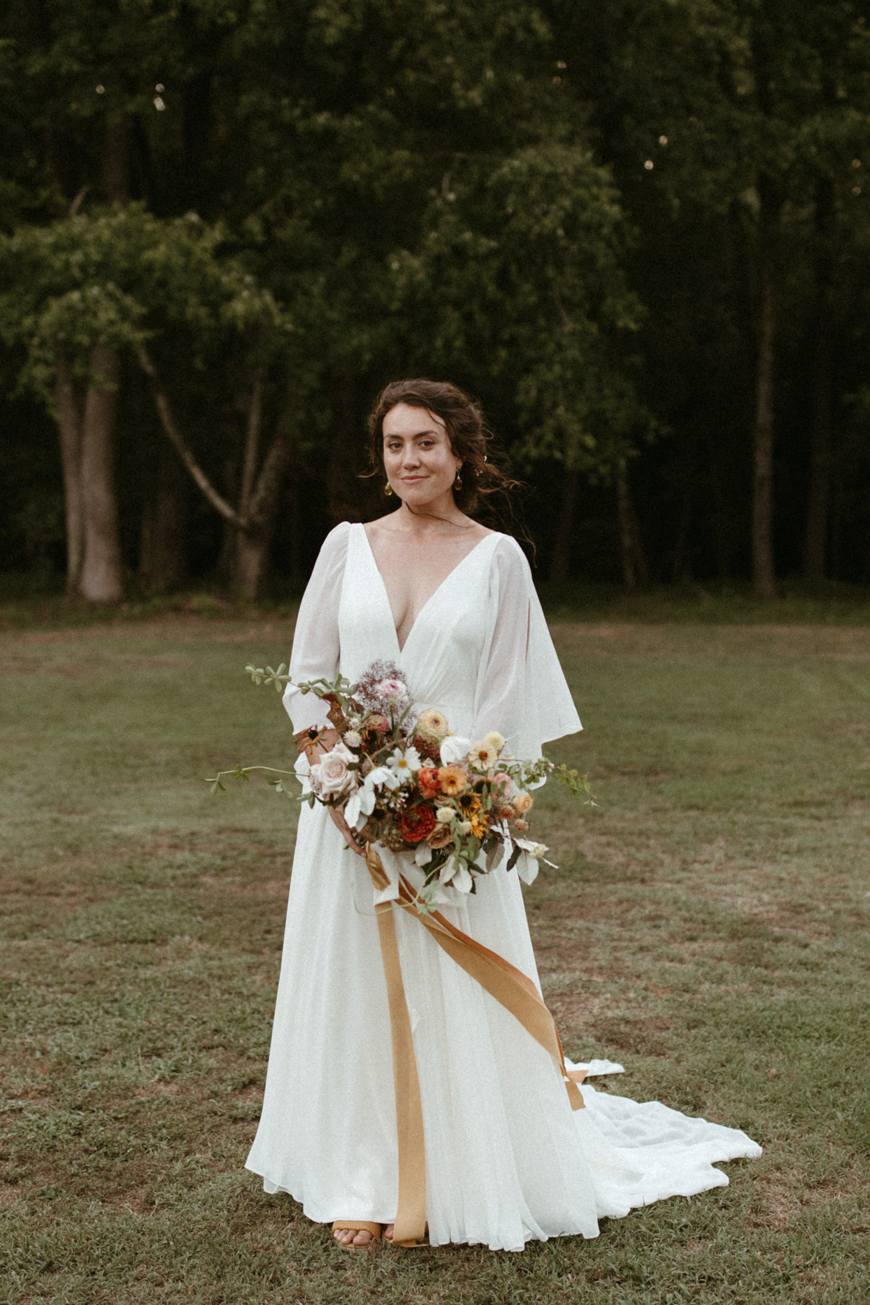 bride wearing long flutter sleeve deep v flowing a-line dress