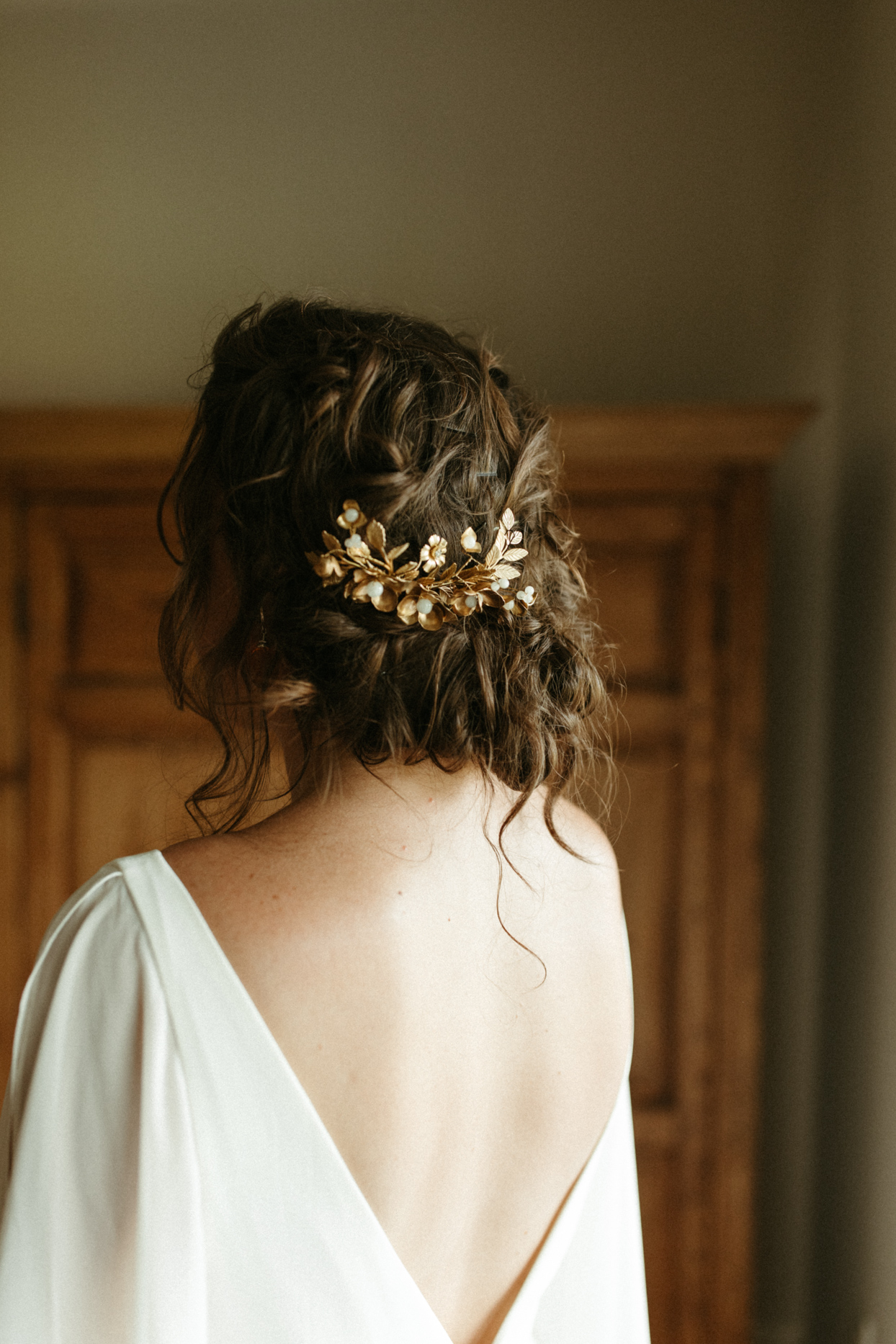 bride wearing gold leaf hair pin in low hair style