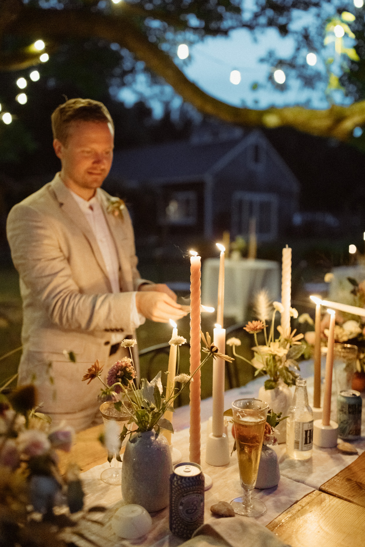groom lighting tapper candles on reception table