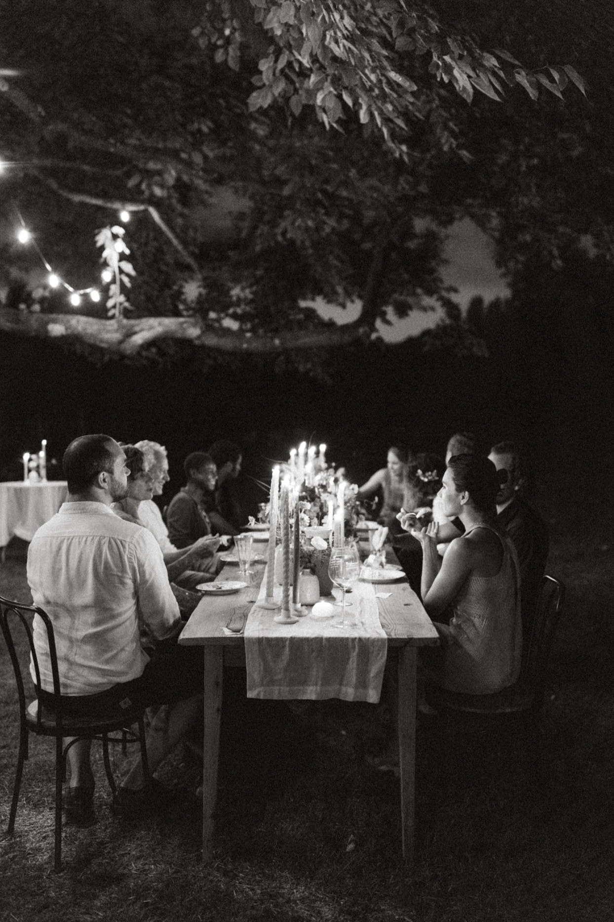 friends and family sit around candle lit reception table outside