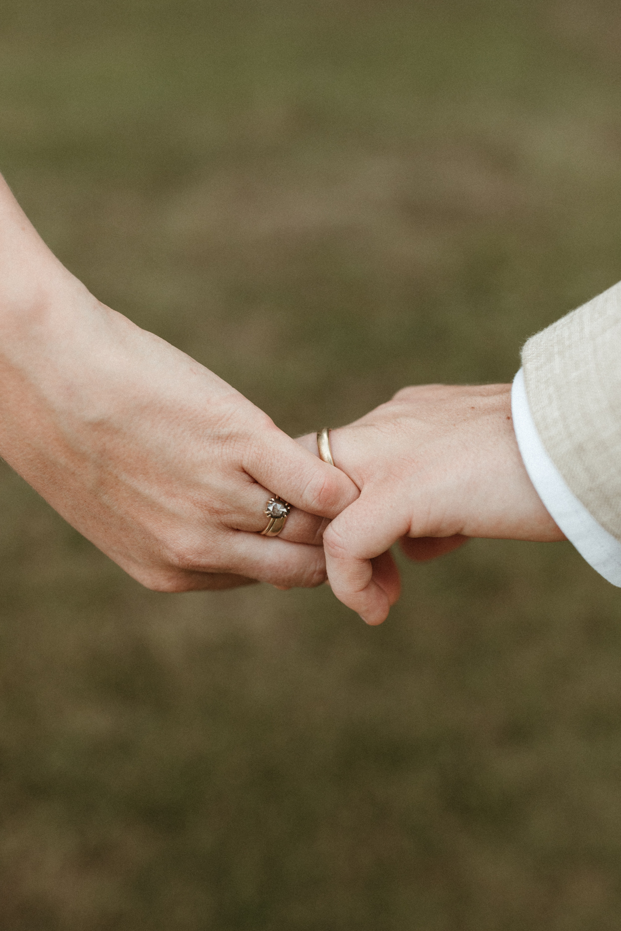 bride and groom hold hands wearing wedding rings