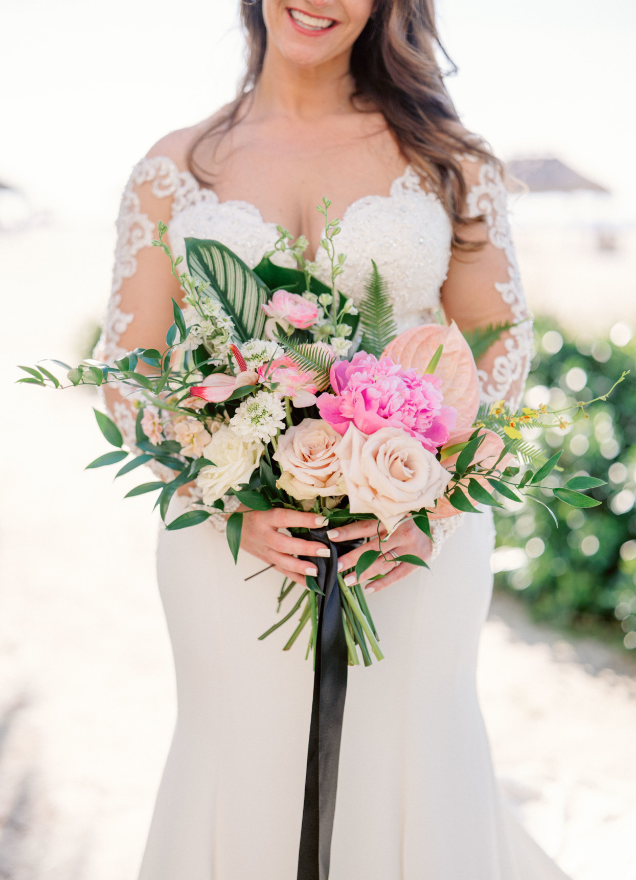 bride's bouquet with pink, cream, and yellow peonies, anthurium, scabiosa, ranunculus, and orchids