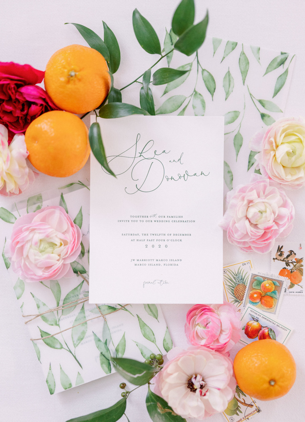 wedding invites with palm-frond green text, a jute tie, and a printed vellum wrap