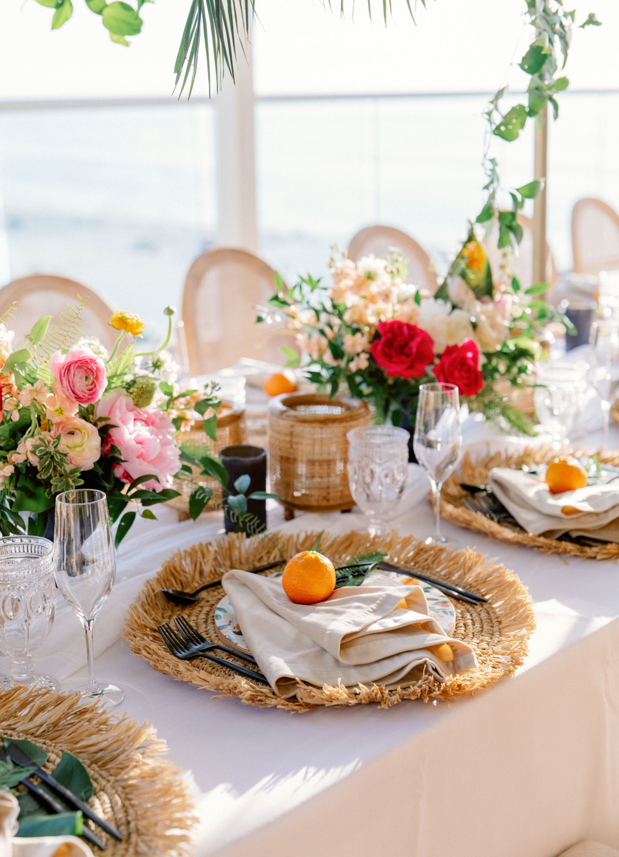 reception tables with floral centerpieces and oranges