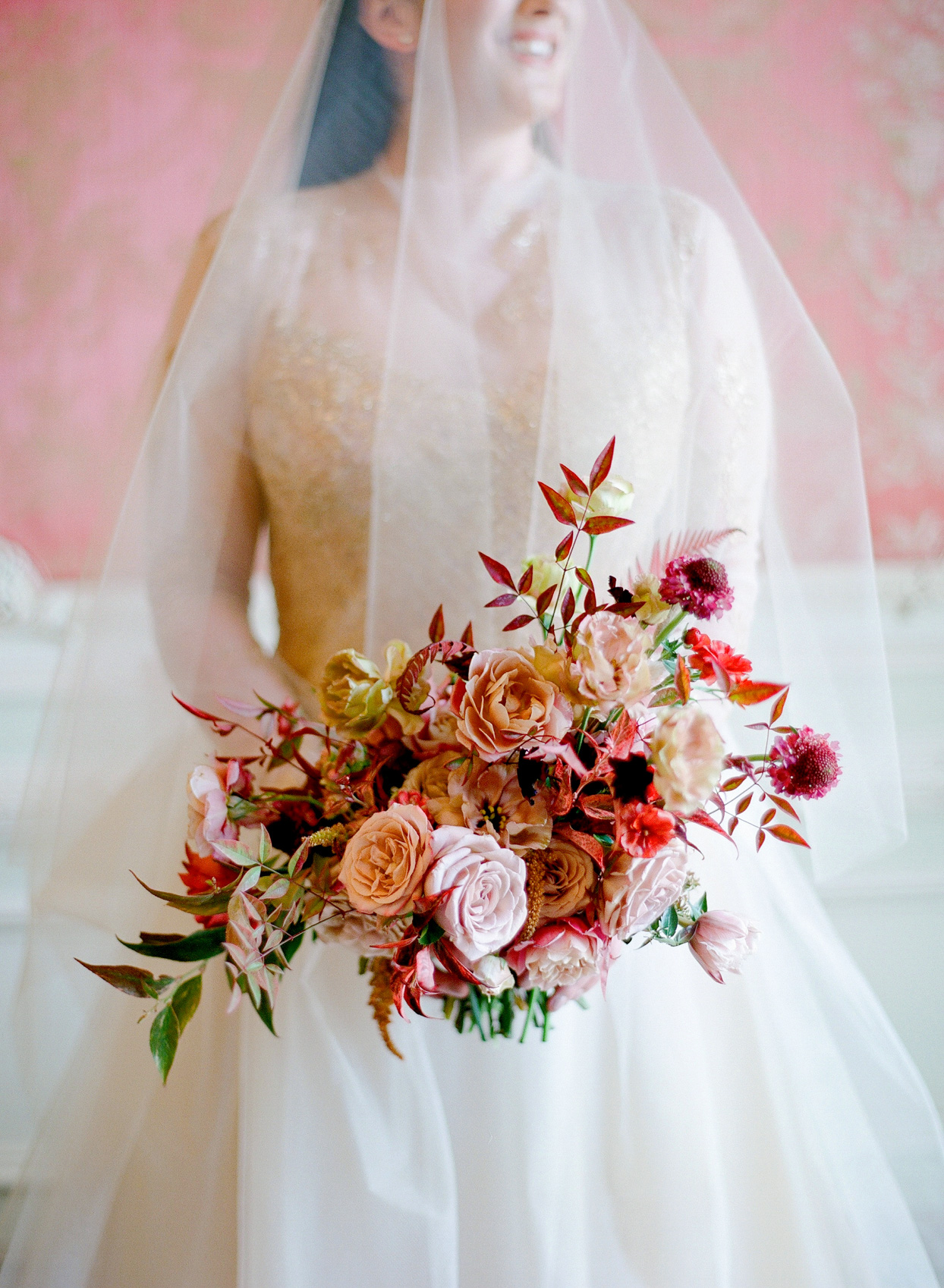 bride in white and gold holing vibrant red and pink bouquet