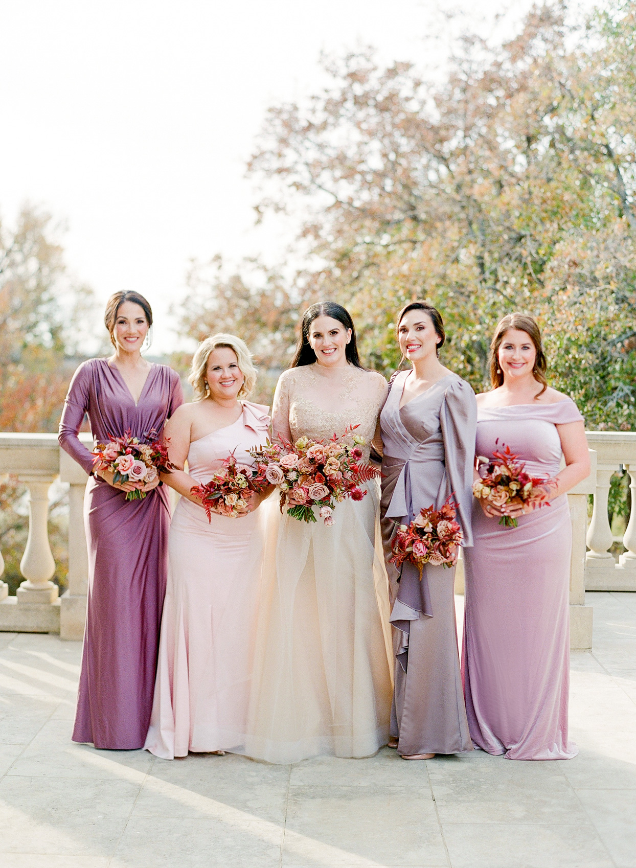 bridesmaids in shades of pink and purple on balcony