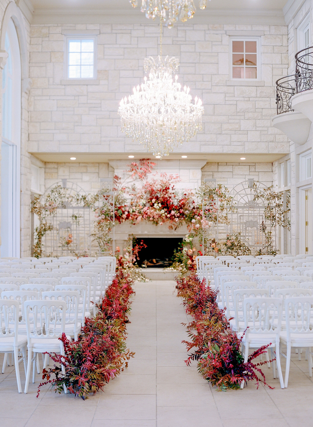elegant indoor wedding ceremony set up with white chairs and red bouquets