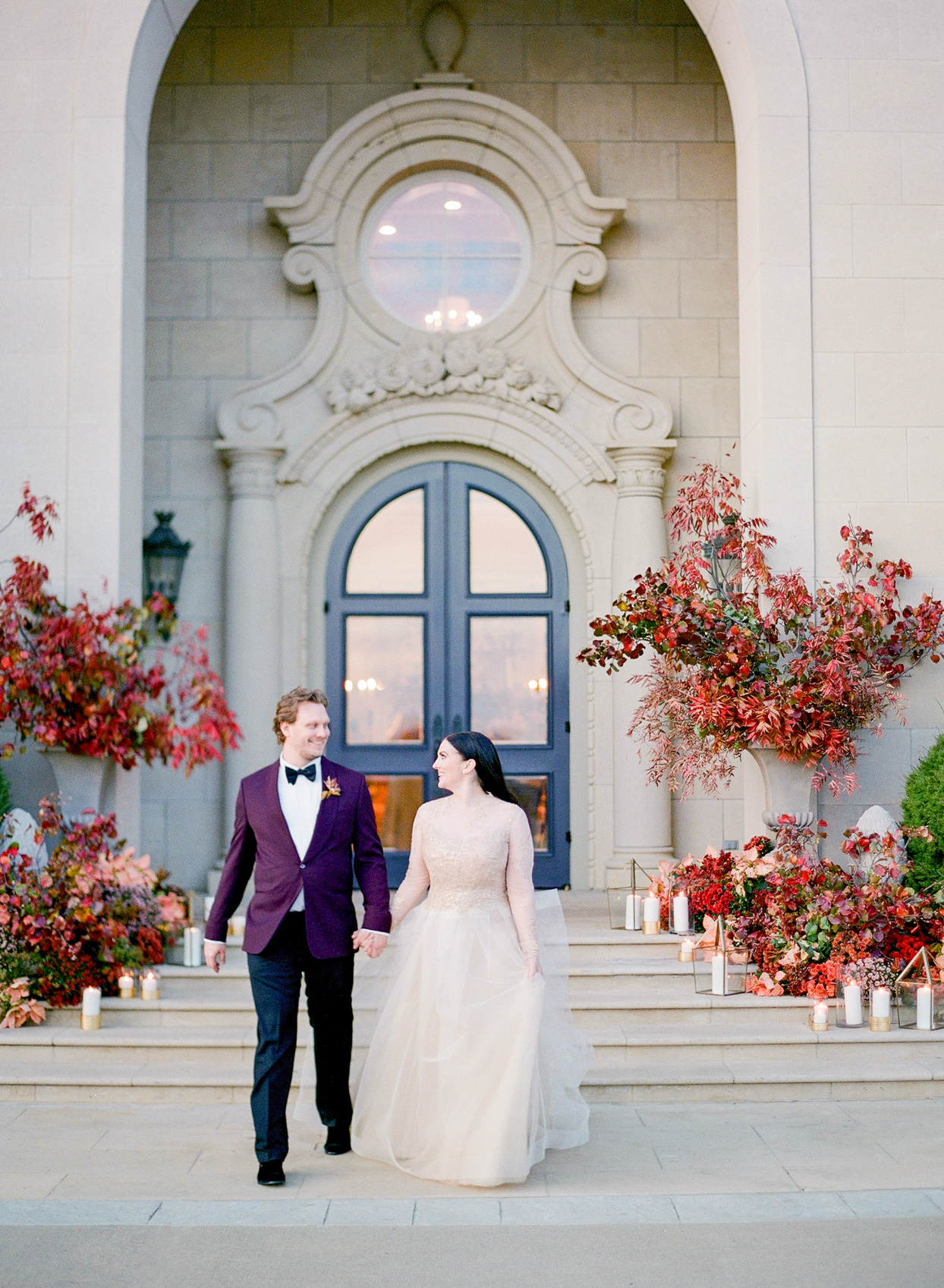 bride in white gold and groom in purple jacket walking together
