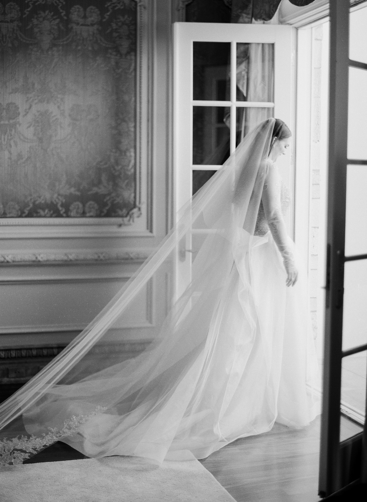 bride walking out french doors with long veil trailing behind her