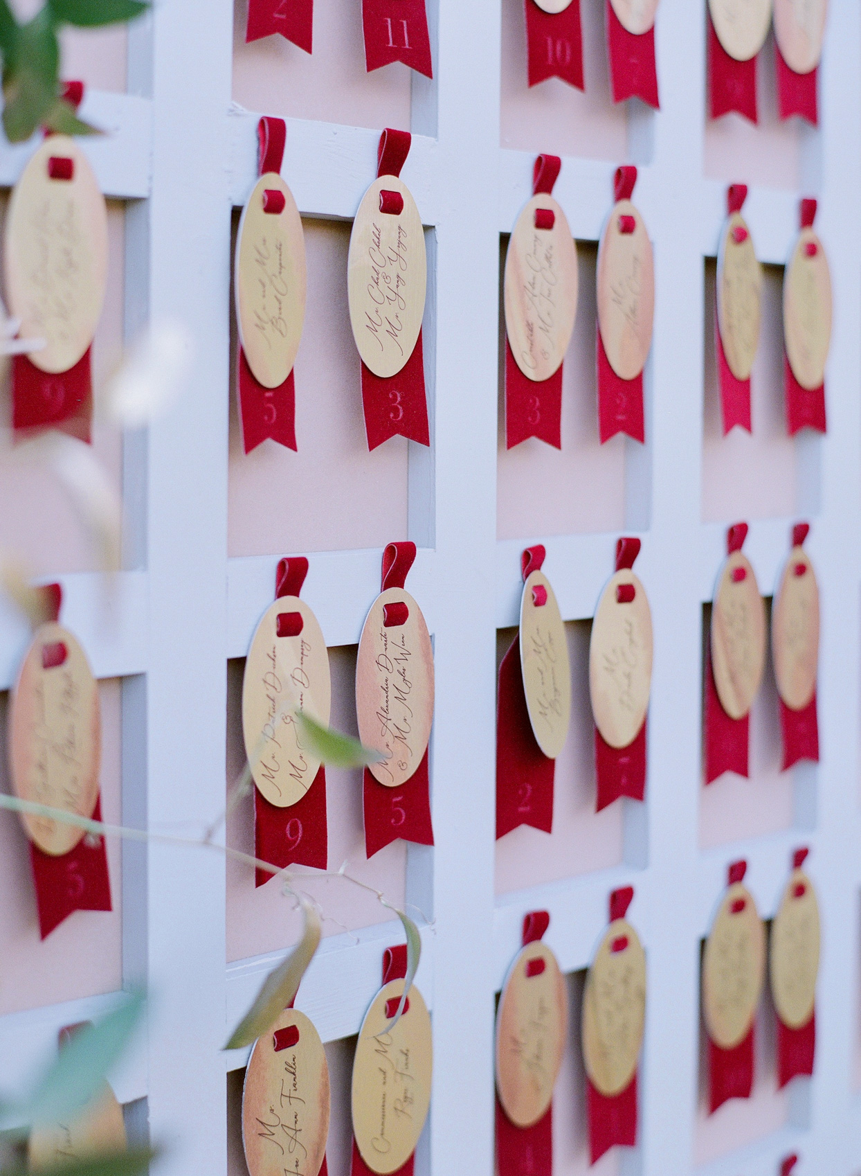 oval escort cards with red velvet ribbons
