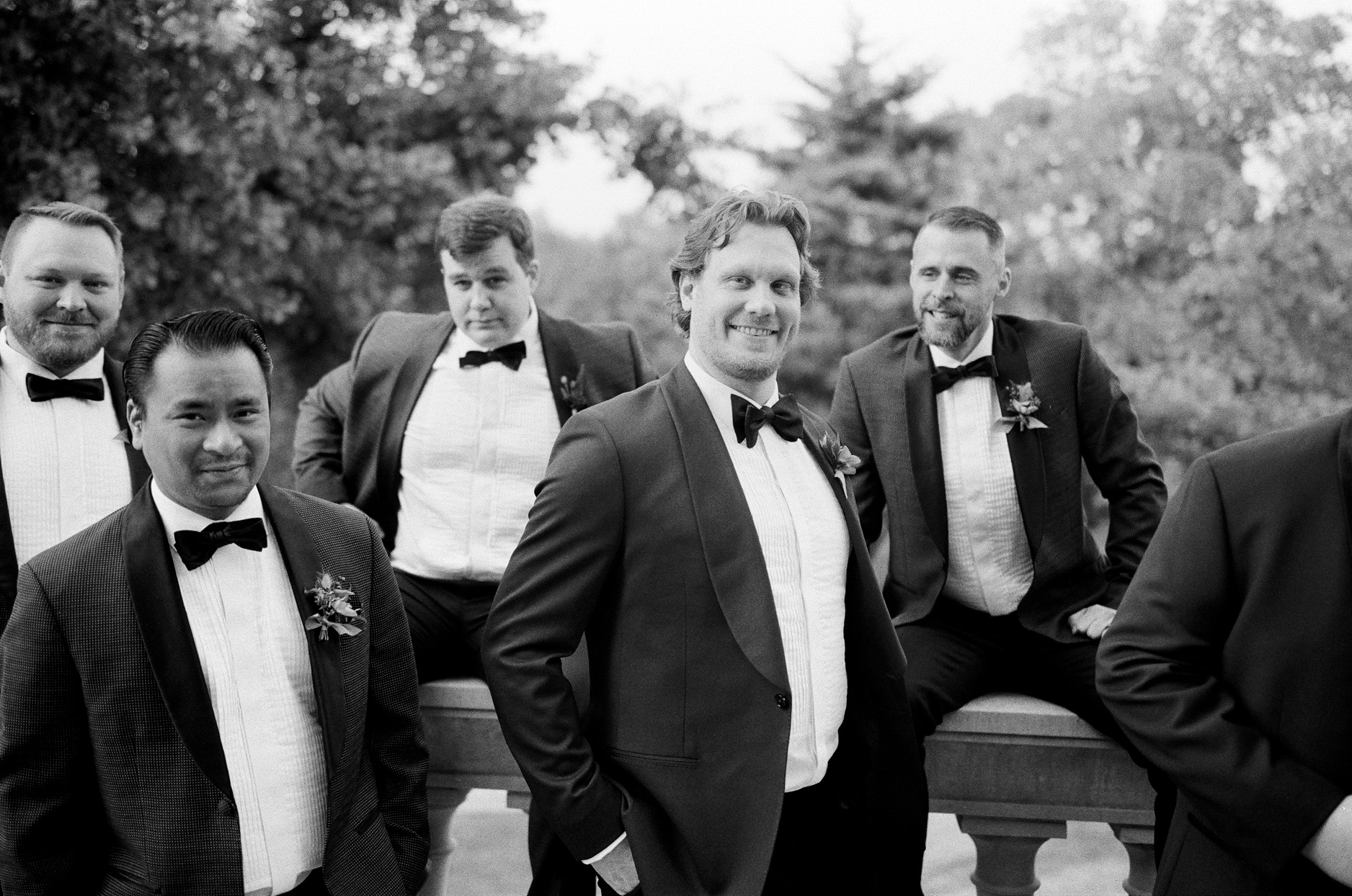 groomsmen in suits and bowties posing on balcony