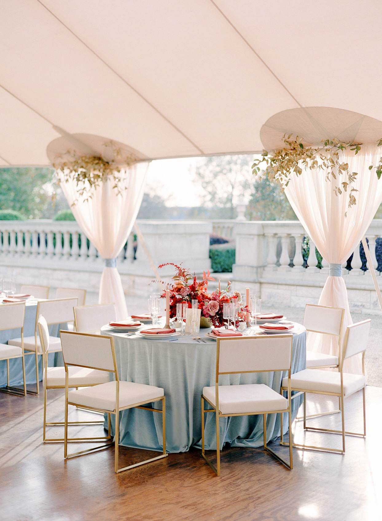 reception round tables with pale blue cloths and red flowers on patio