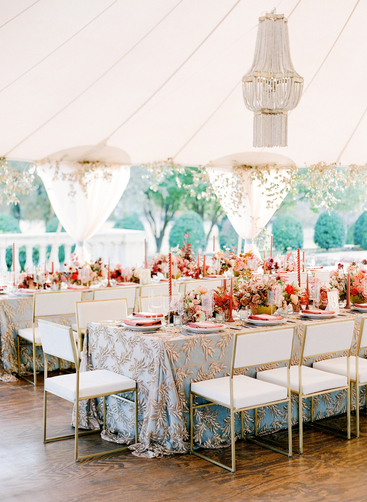 long tables for wedding reception with blue and gold clothes and red decor