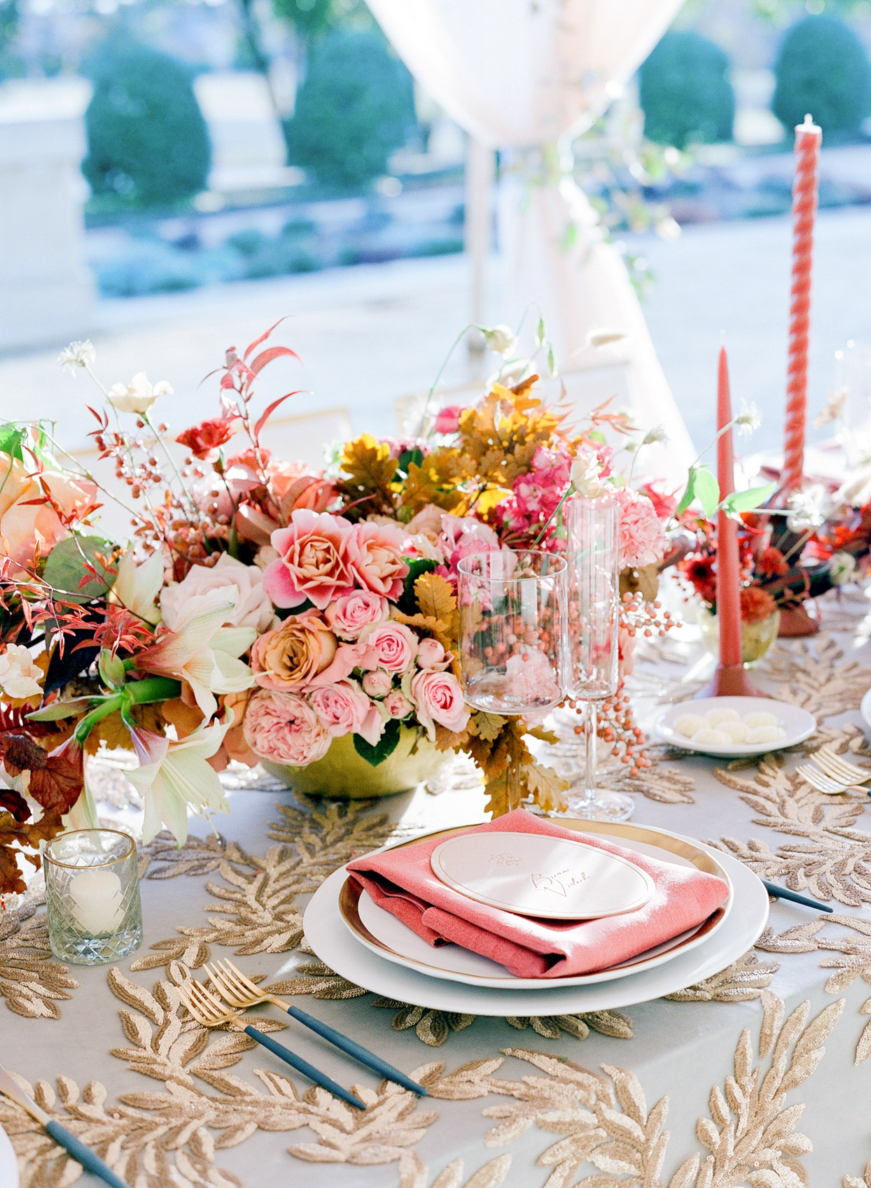 detail shot of wedding table with blue and gold cloth and red decor
