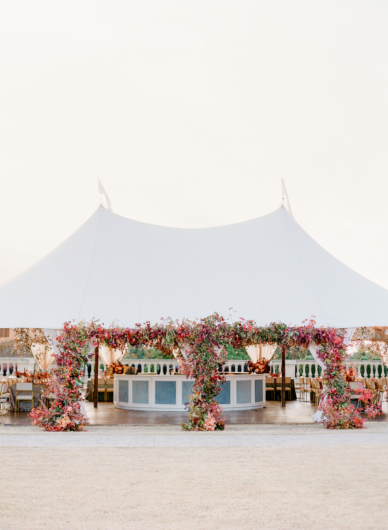 large white wedding tent with vibrant red florals