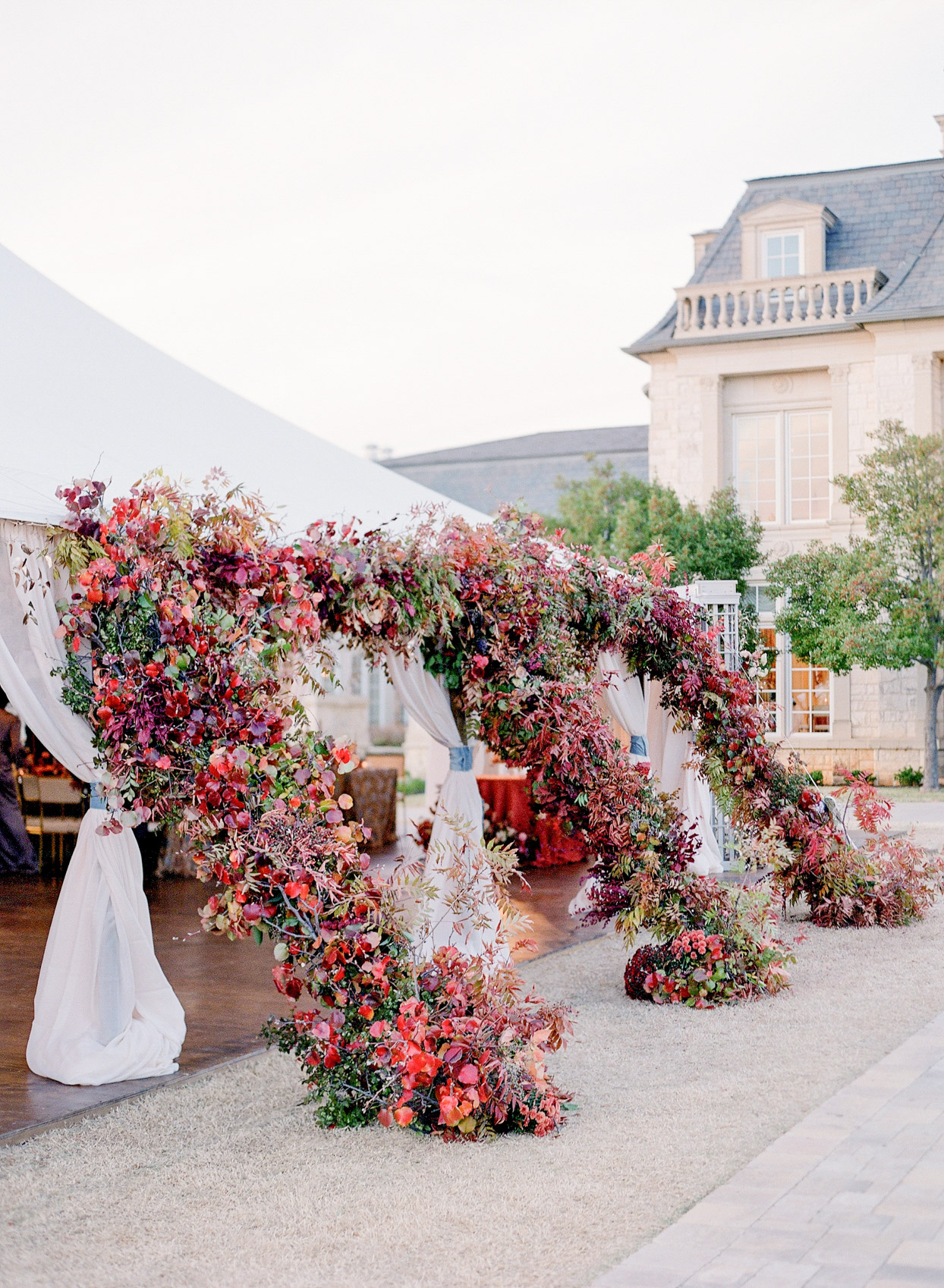 large floral installments coming off of white wedding tent