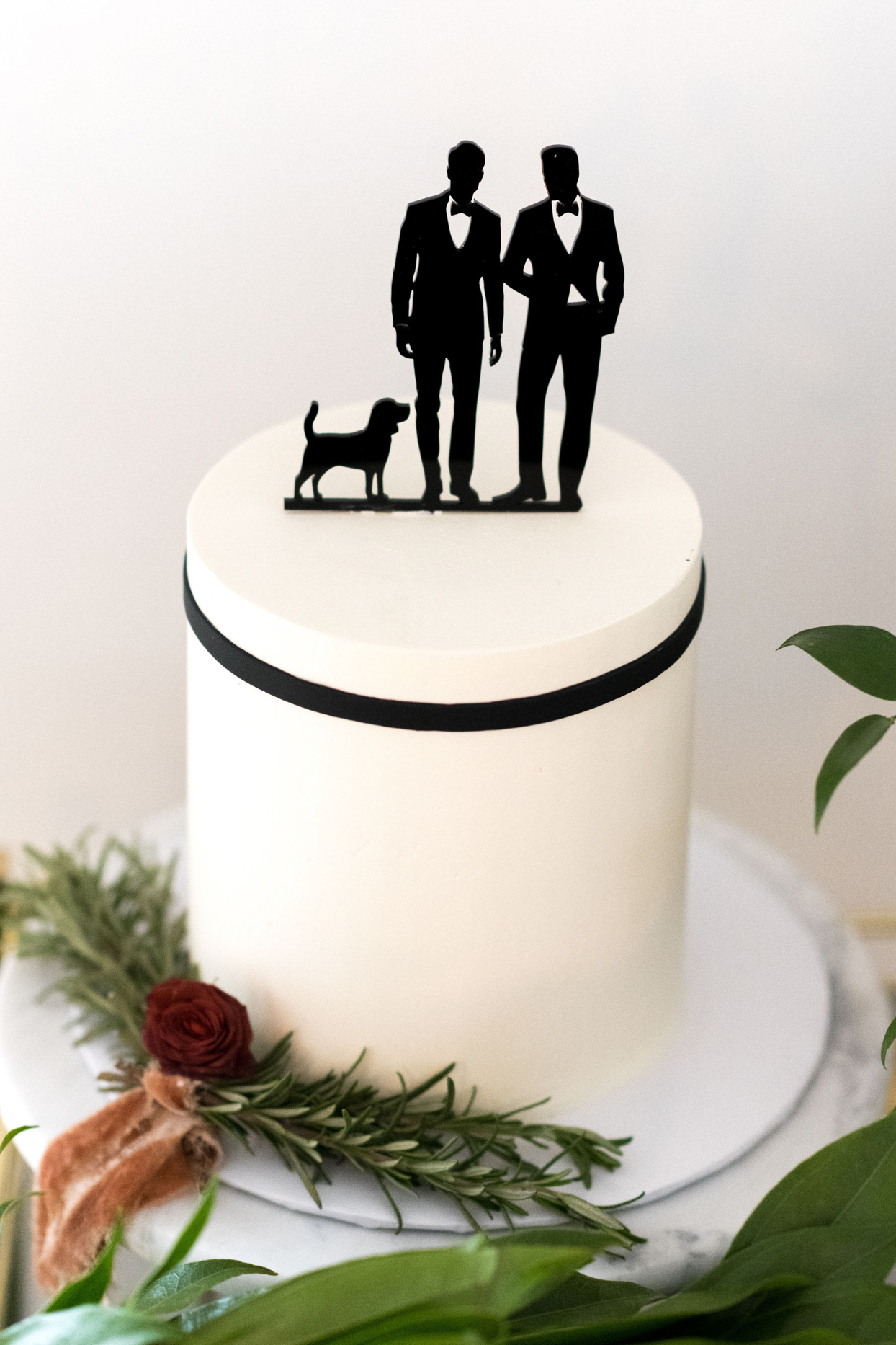simple black and white wedding cake with grooms topper