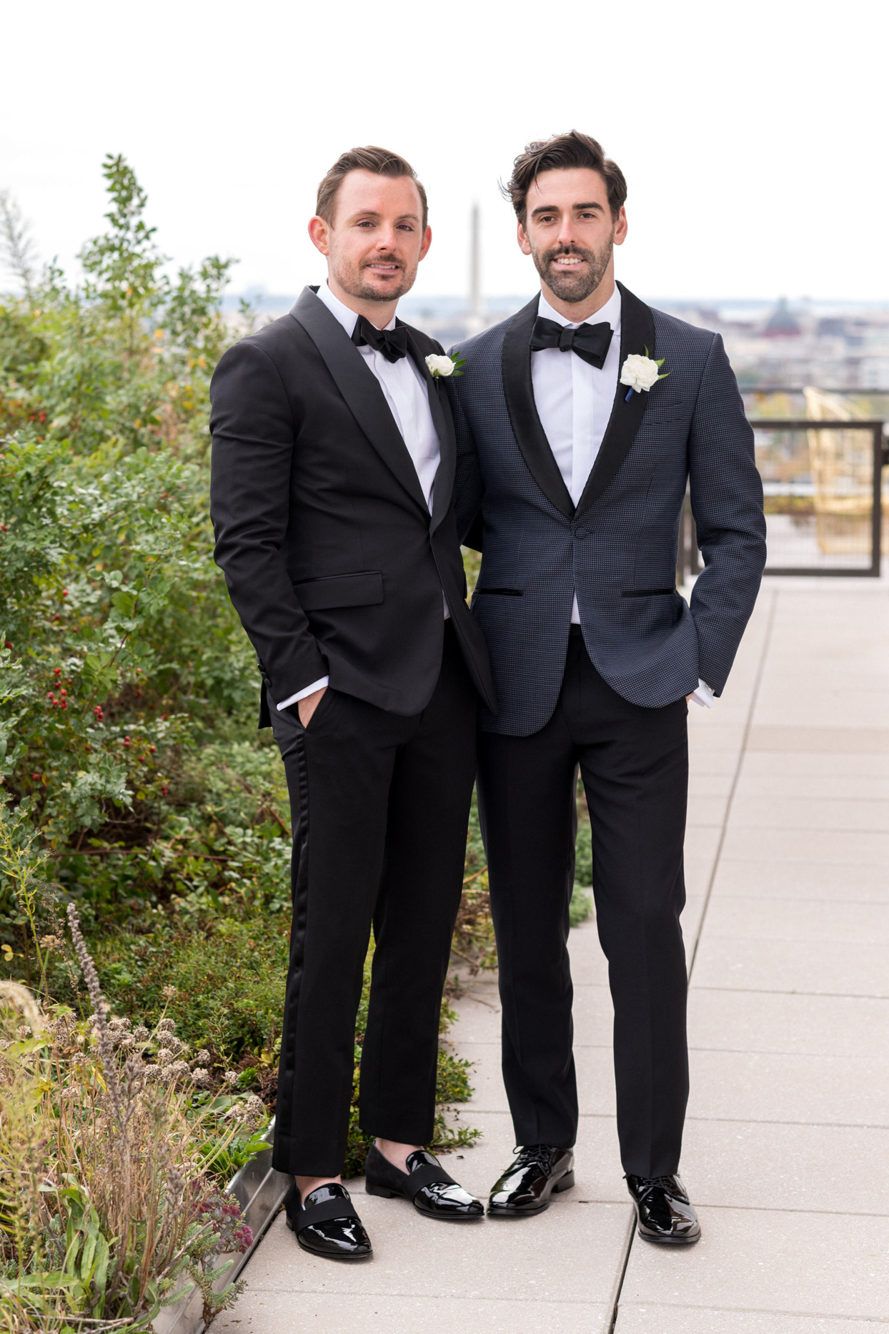 wedding grooms in black tuxes on rooftop