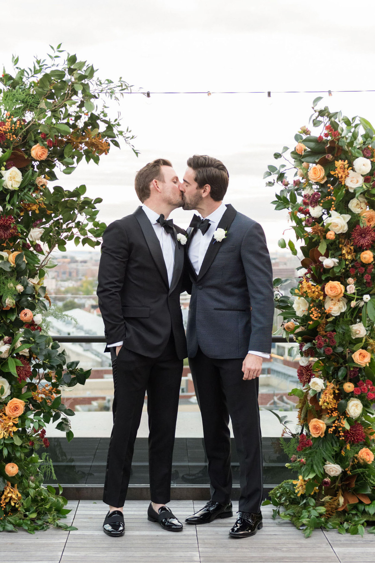 grooms kissing at rooftop wedding location under floral arch