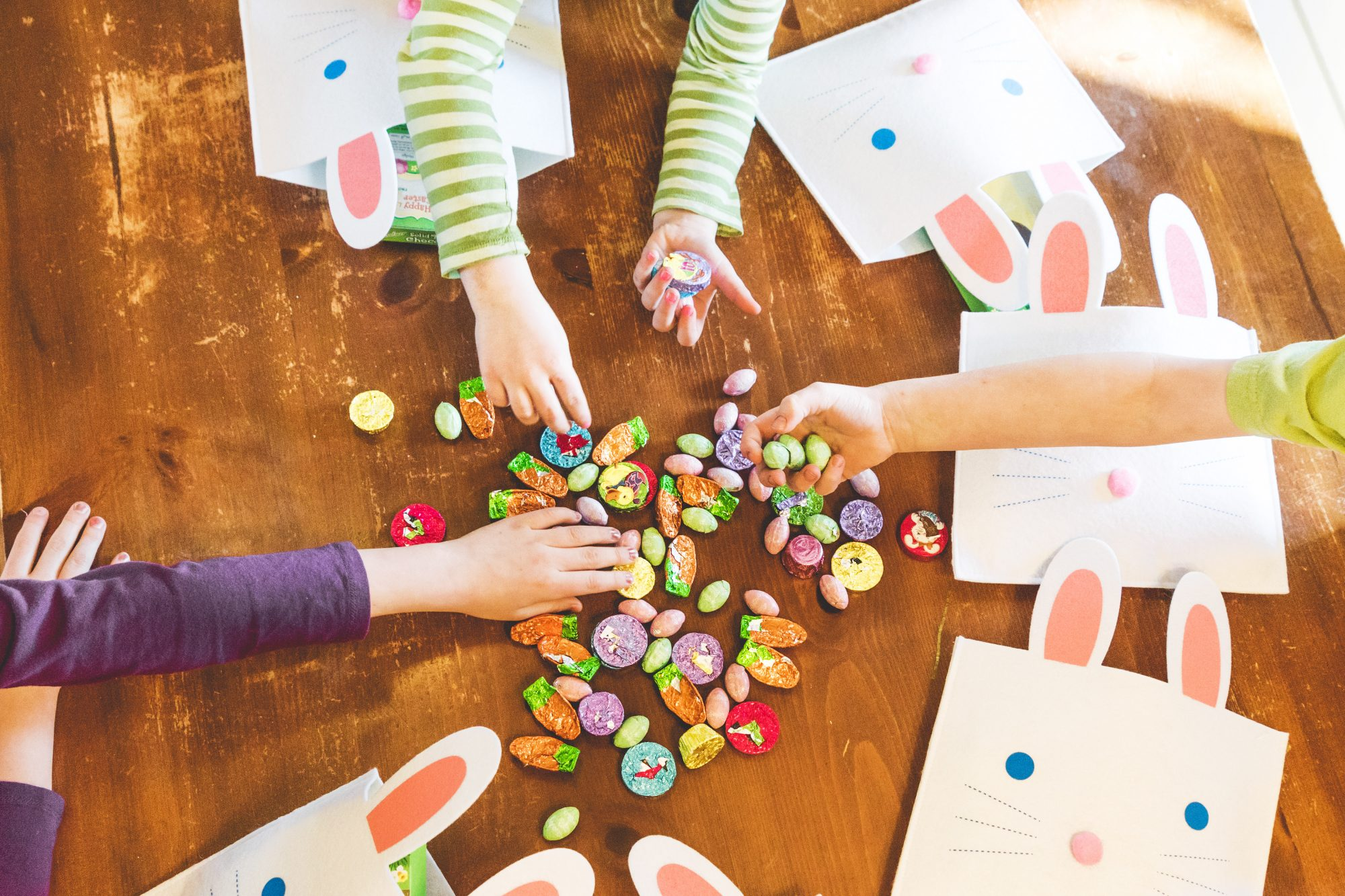 kids reaching for pile of easter candy on table
