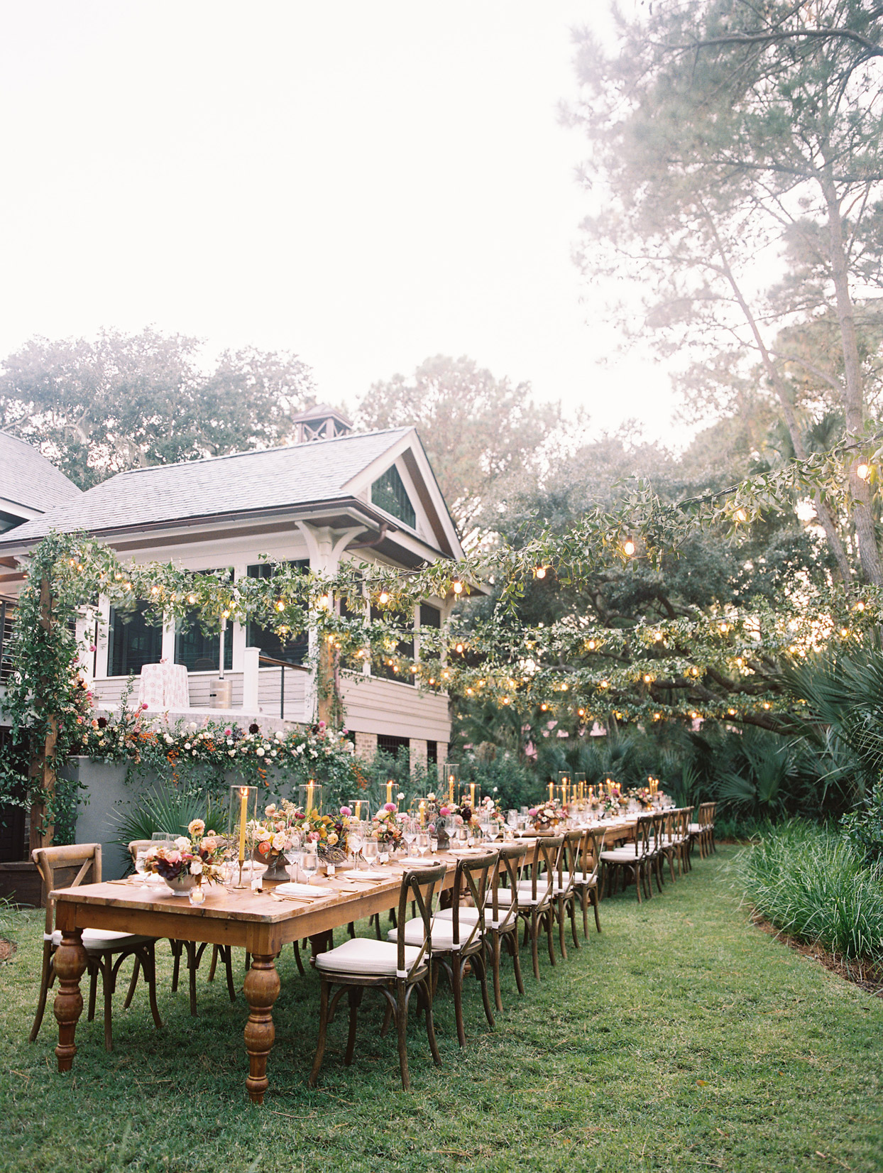 elegant rustic outdoor reception set up with long wooden tables and lit greenery garlands