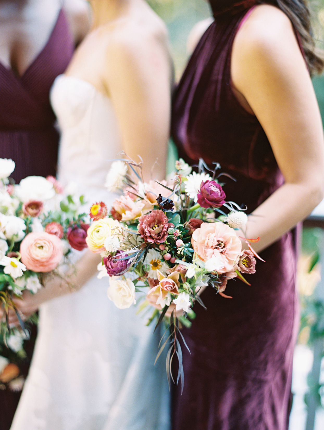 bridesmaids in deep burgundy dresses holding pink, yellow, and purple floral bouquets