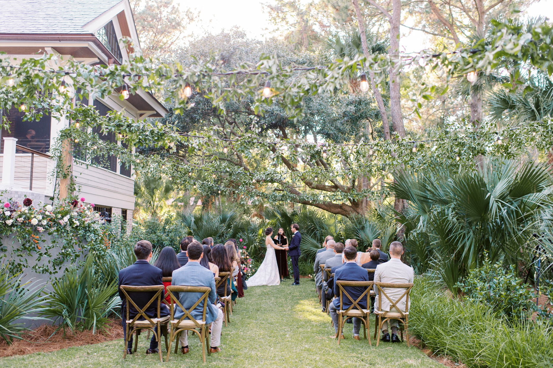 small outdoor ceremony in backyard with wooden chairs