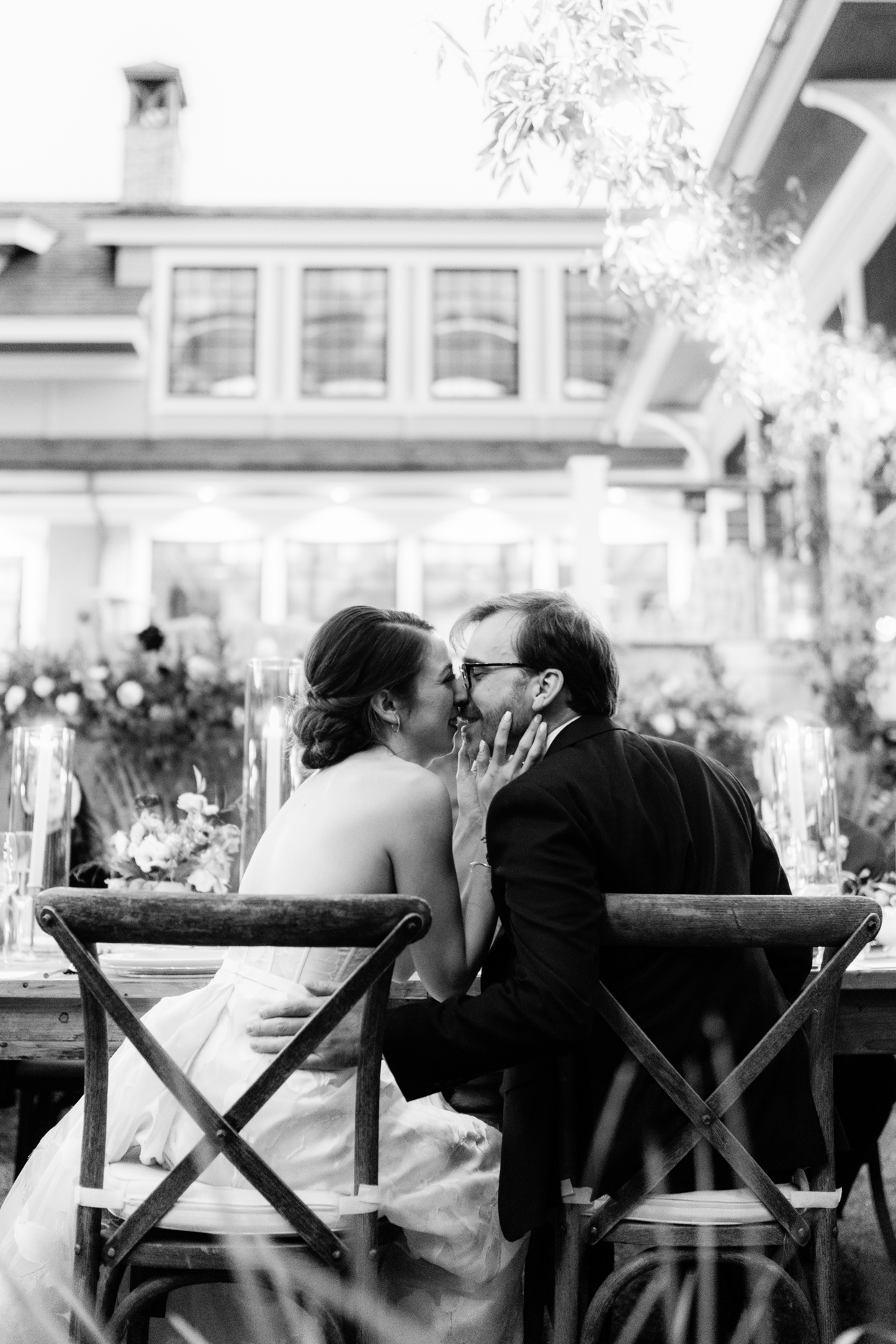 wedding couple kissing at wooden table during reception