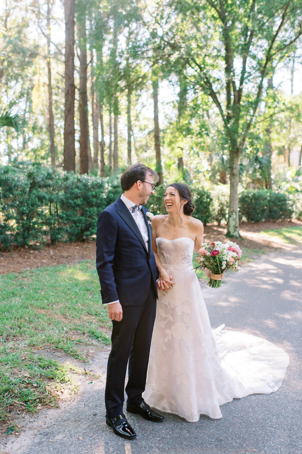 couple holding hands and smiling at each other during first look