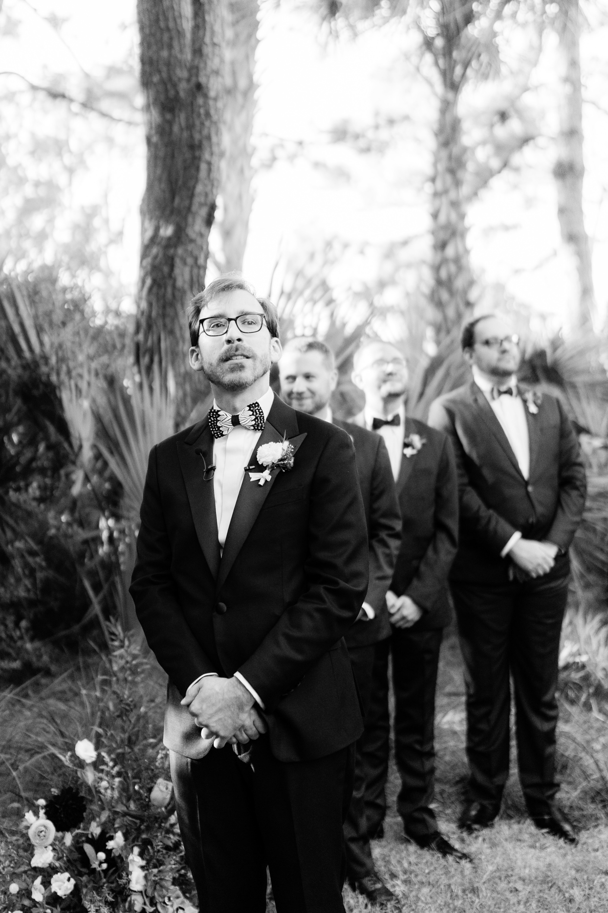 groomsmen in black suits staggered portrait in the forest