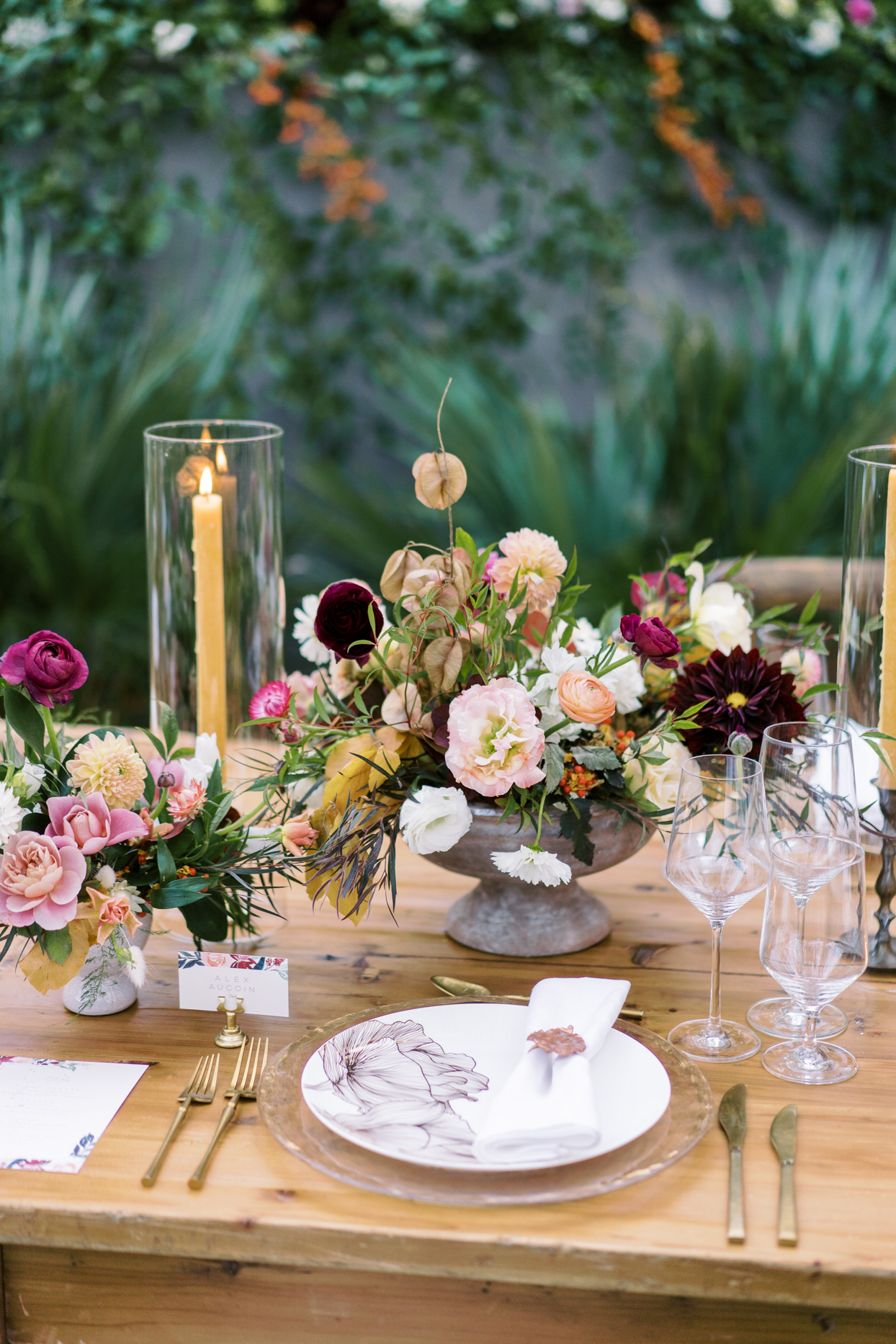 floral place setting at outdoor wooden reception table