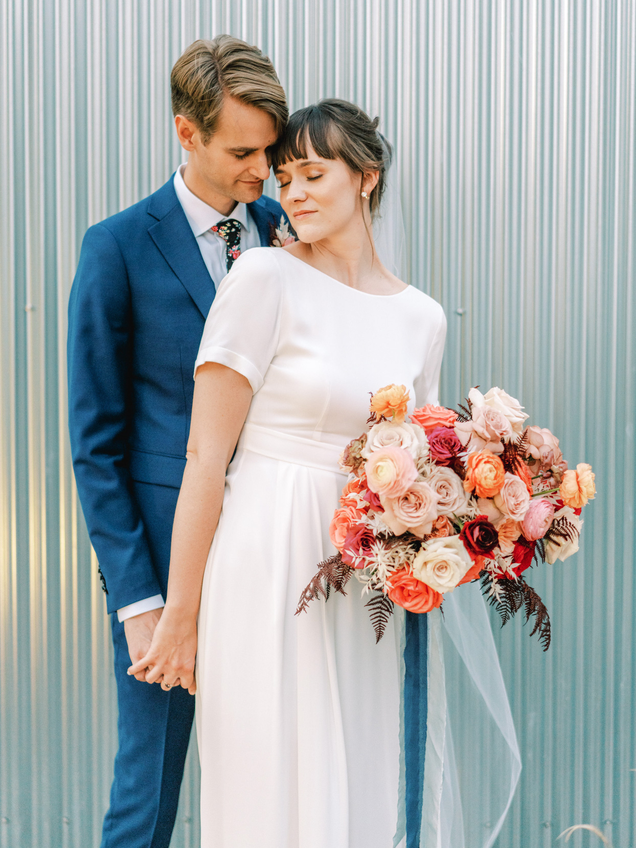wedding couple portrait in front of metal siding wall
