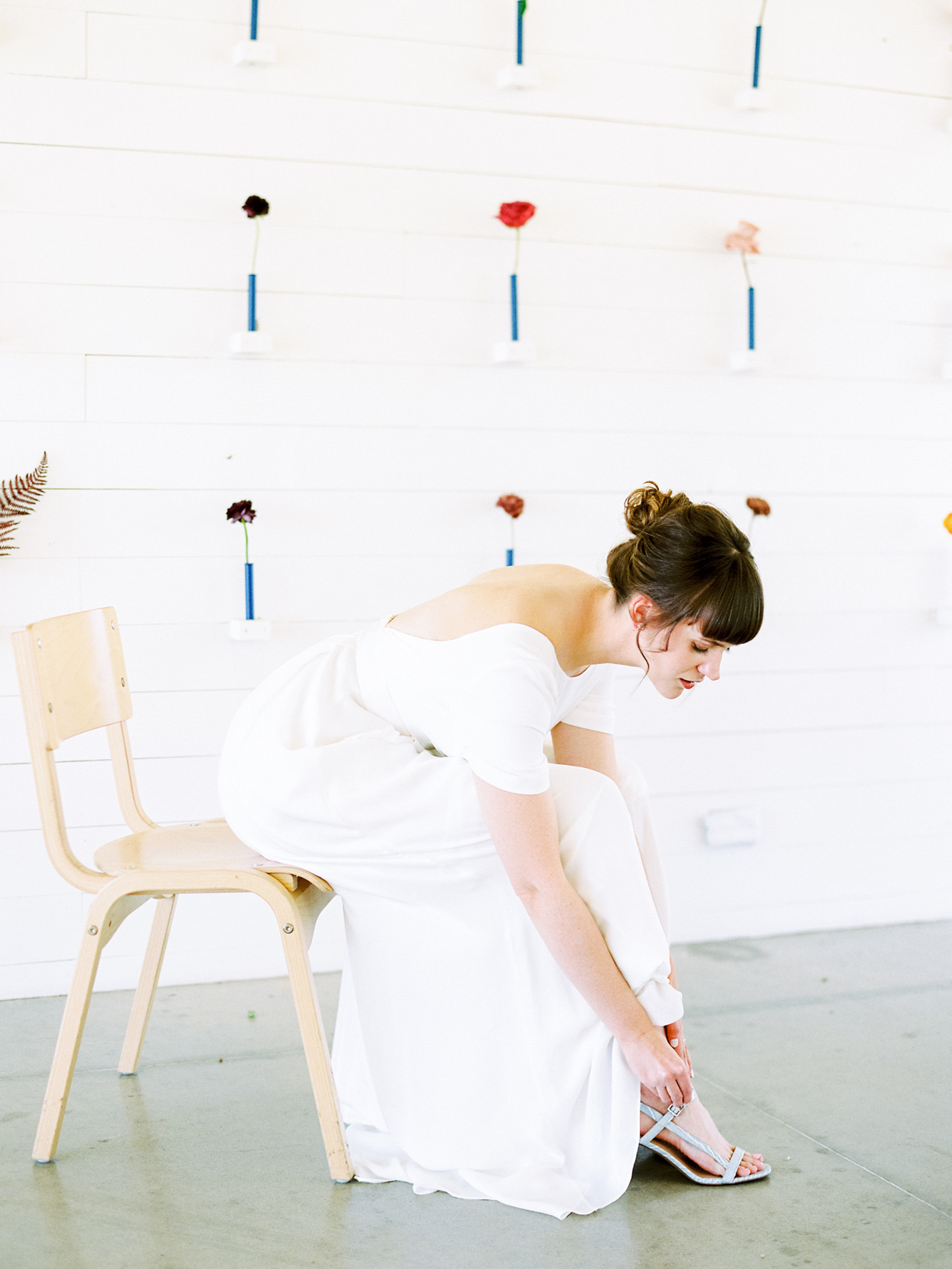 bride sitting on chair putting on shoes with white minimally decorated flower wall behind her
