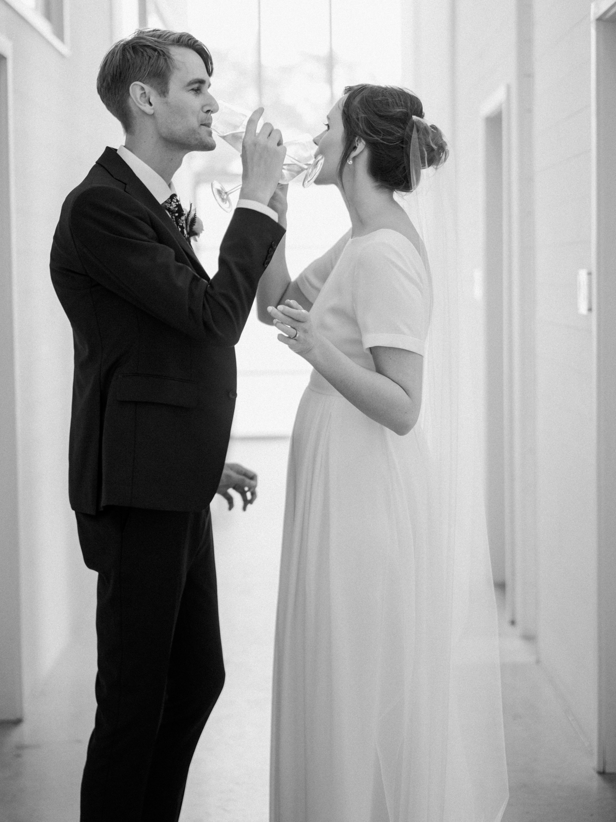 bride and groom drinking champagne in hallway