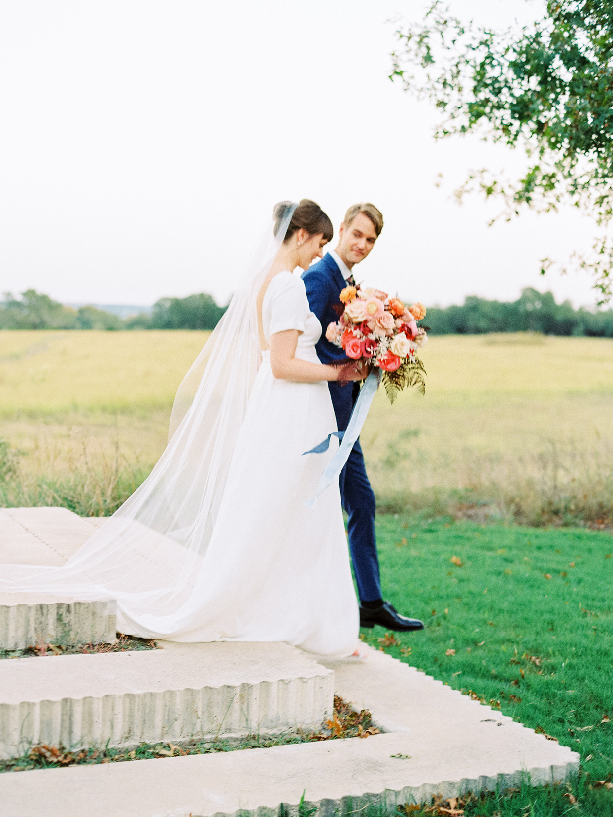 couple walking down stone steps from ceremony location into grassy field