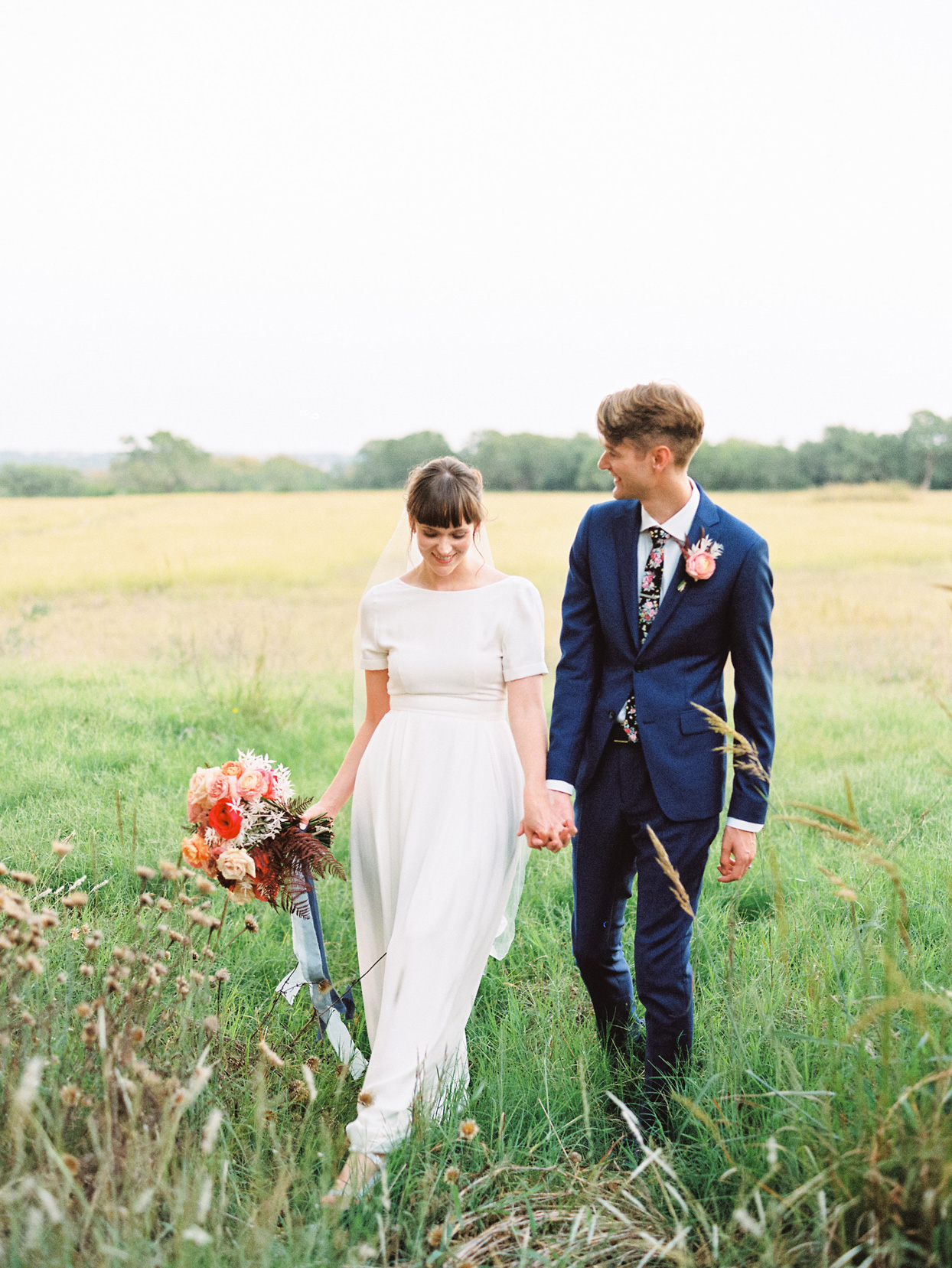 couple holding hands for wedding portraits in wild field
