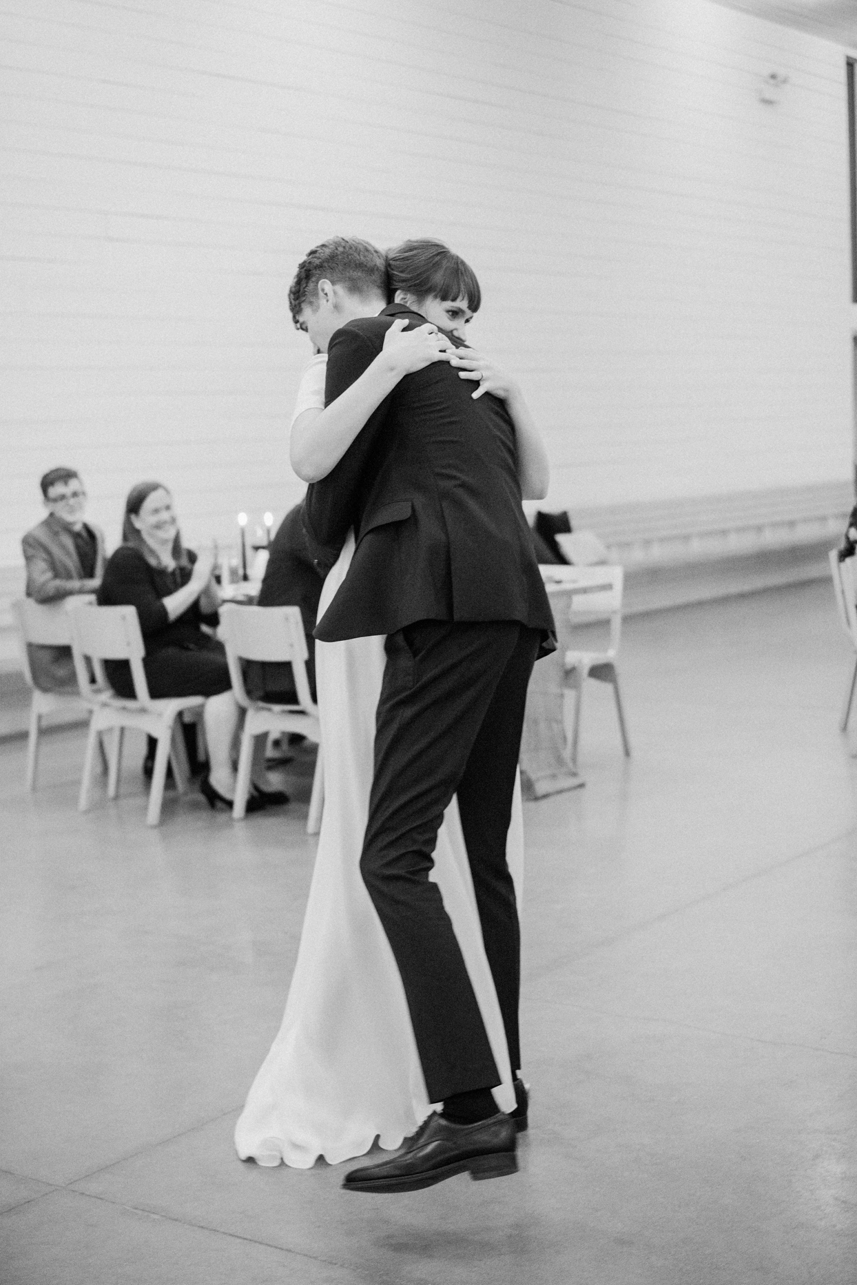 couple hugging tightly as they dance at wedding reception