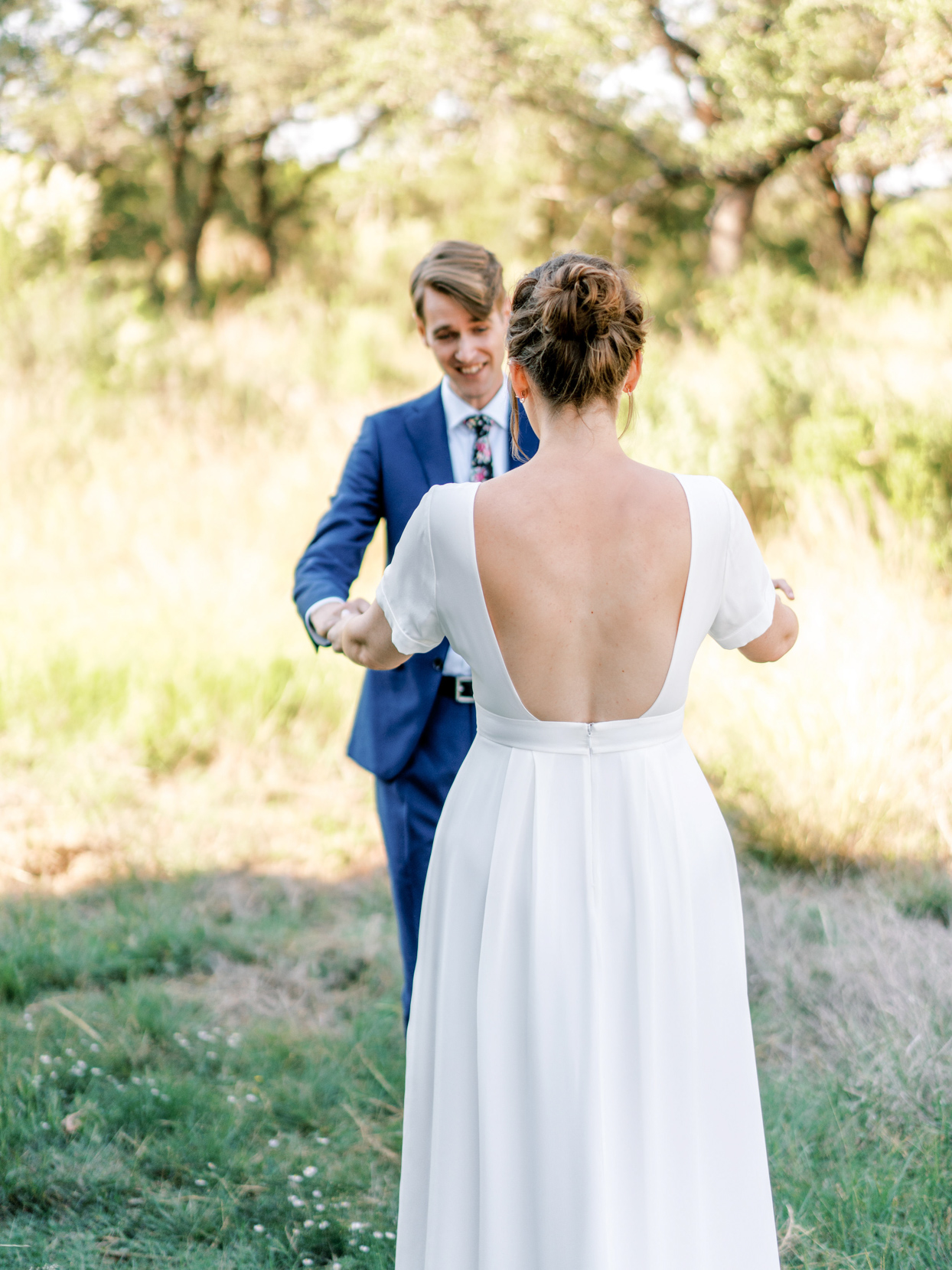 bride and groom holding hands during outdoor first look