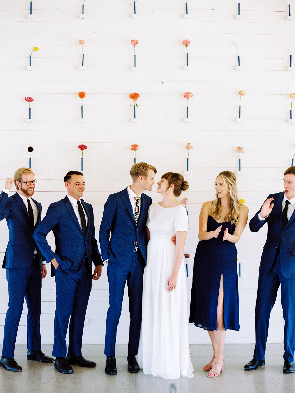 wedding party in blue in front of white minimalist flower wall