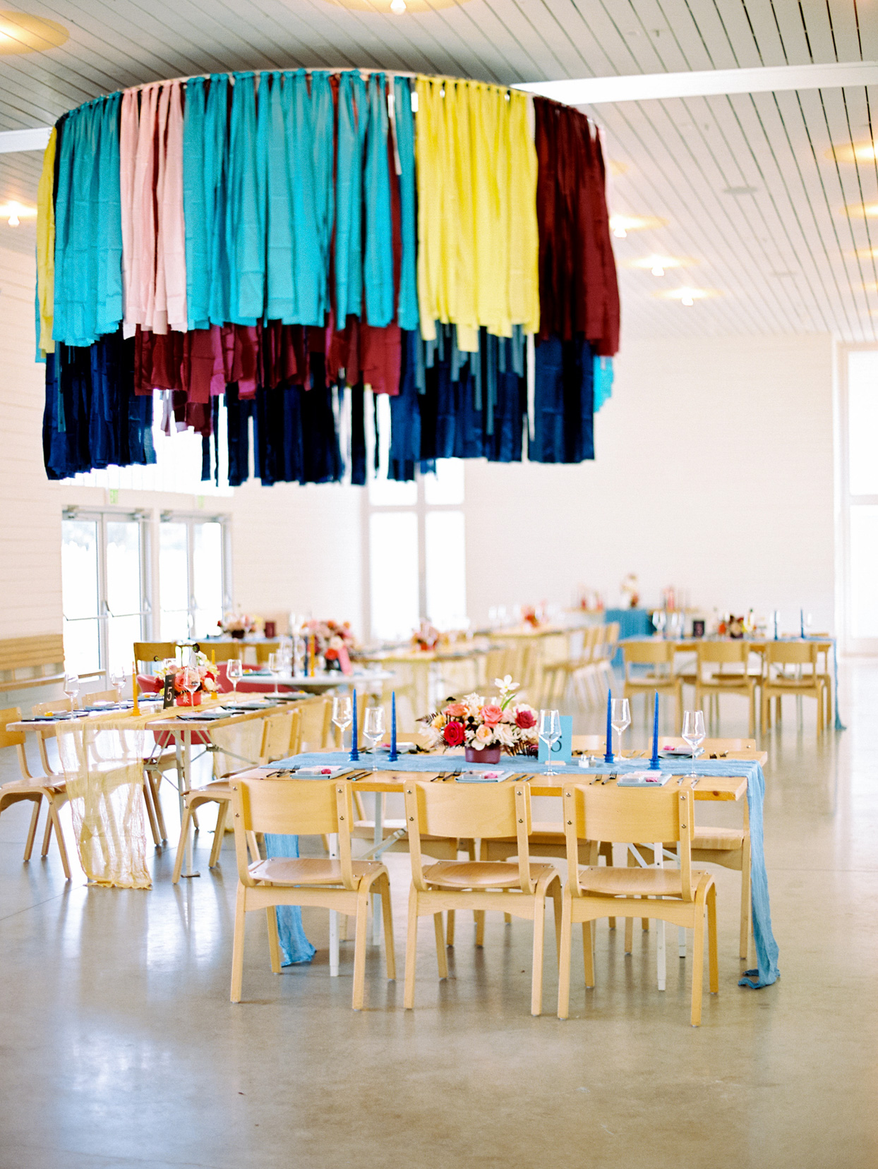 modern open wedding reception area with wooden tables and blue and pink decor