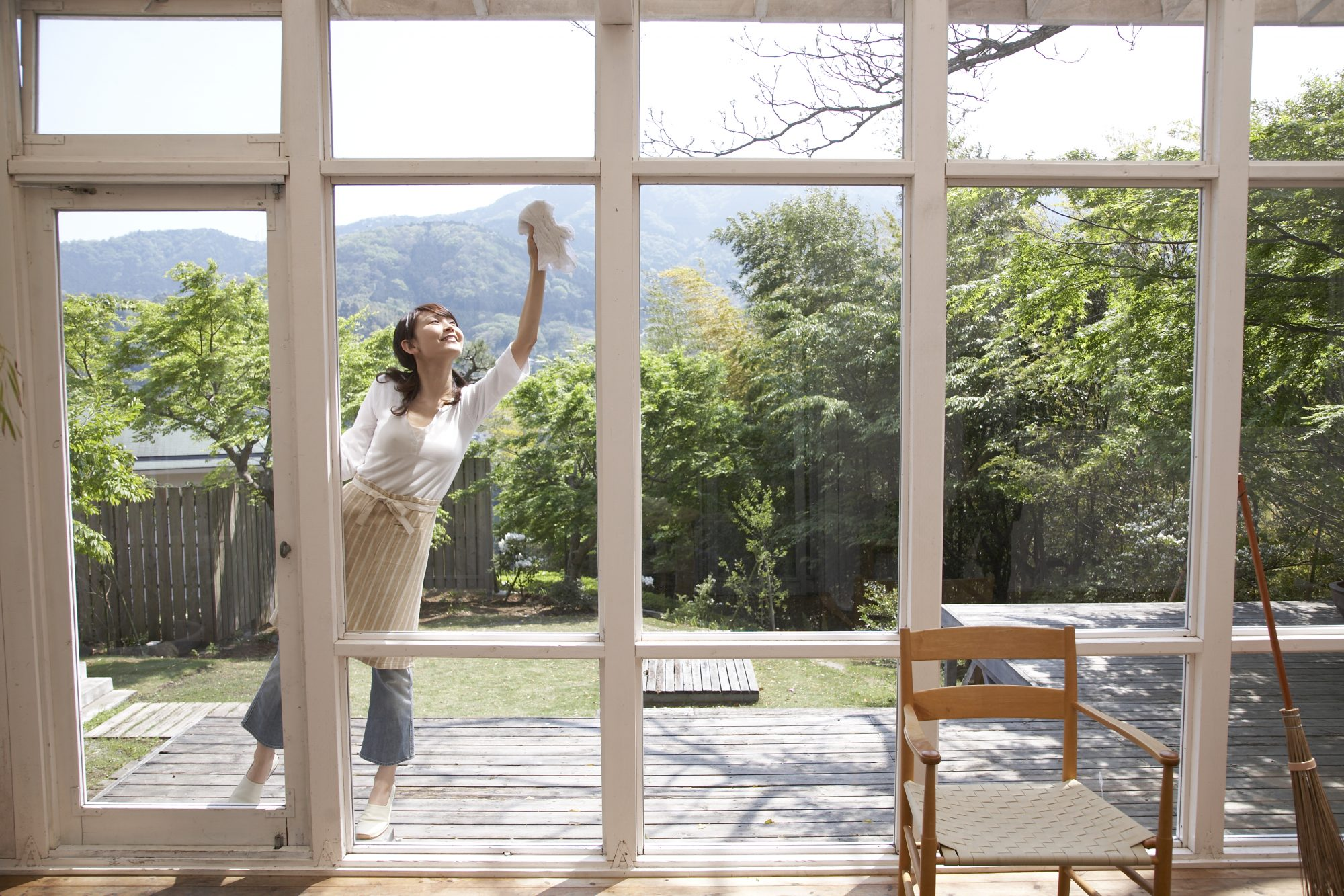 woman cleaning exterior home windows