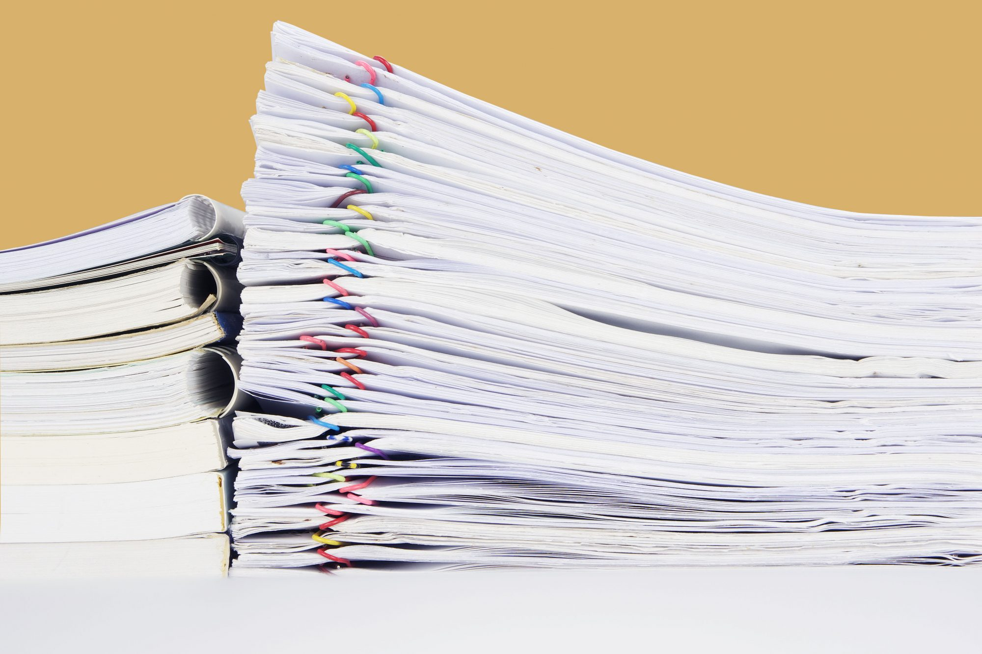 stacked pile of tax paper work on table