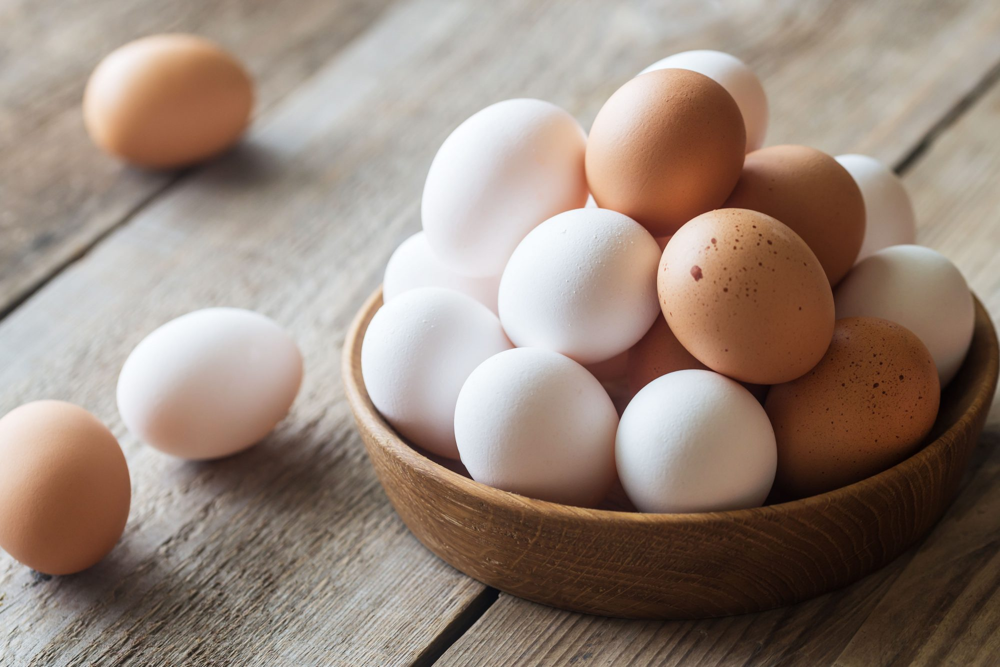 white and brown eggs in wood bowl