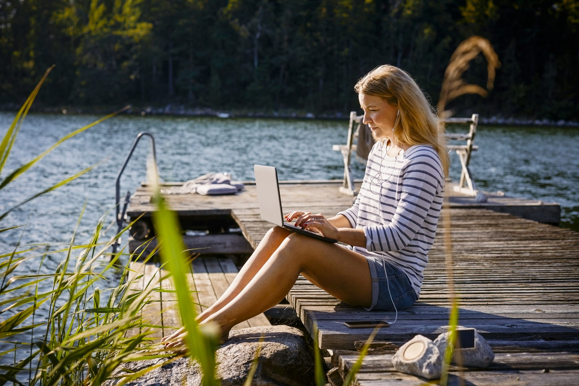 woman working remotely outdoors on lake dock