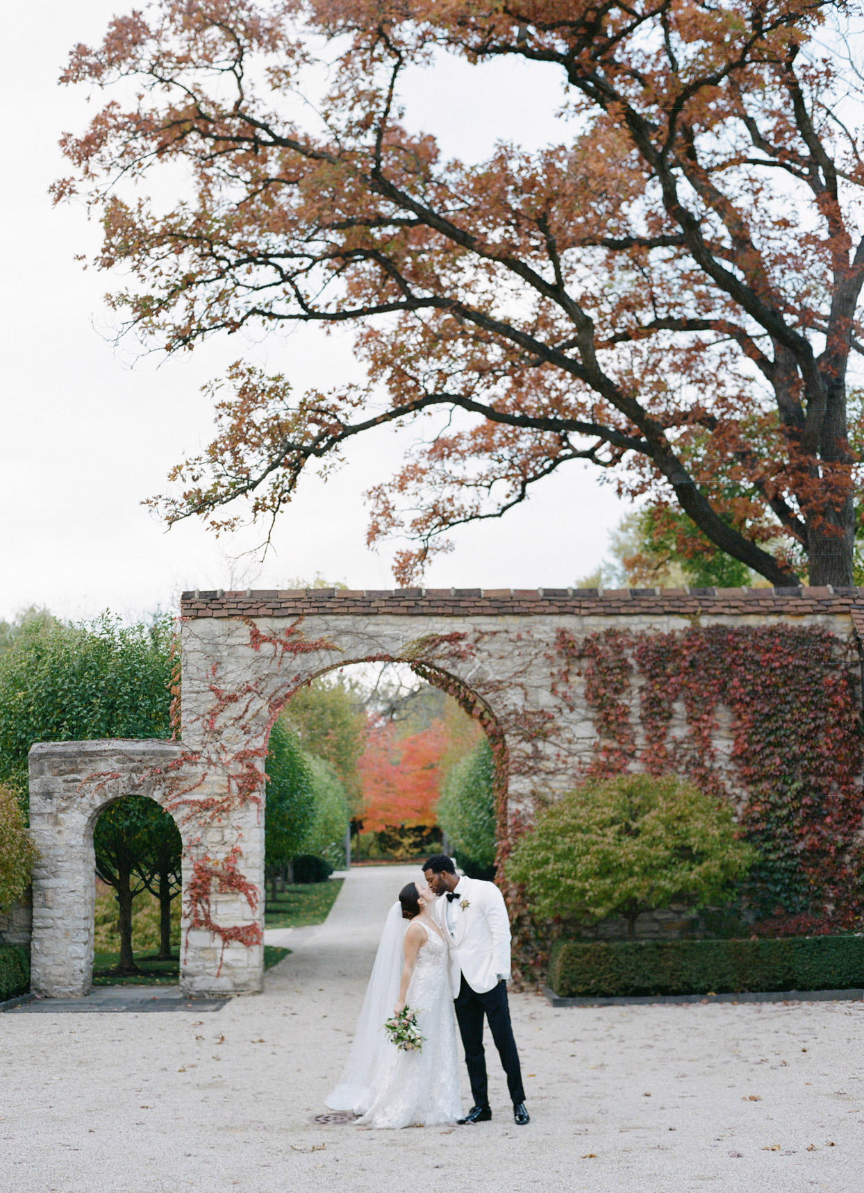 bride and groom kissing in brick archway