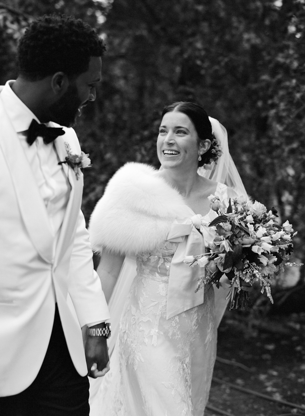 bride and groom smiling holding hands