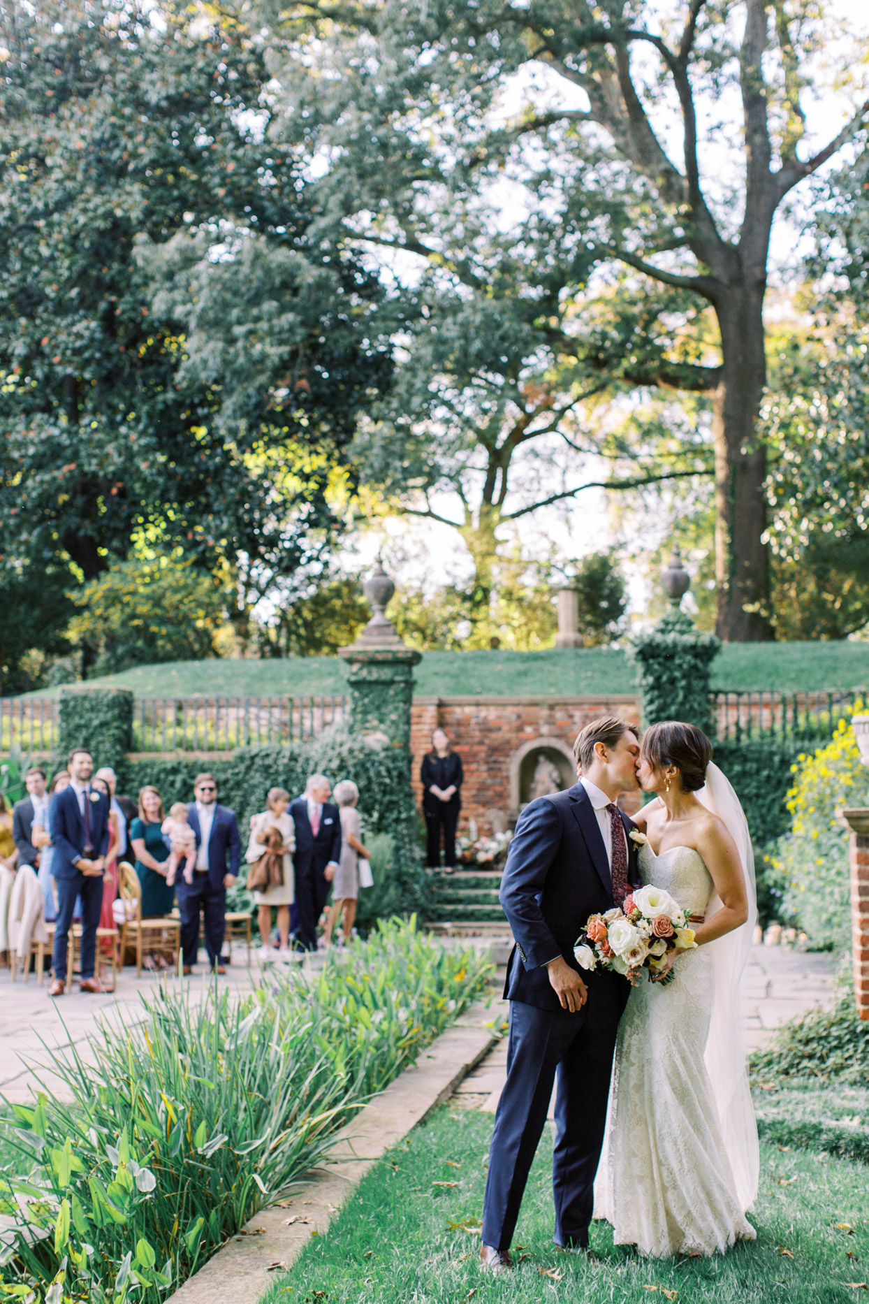 couple kissing during garden wedding ceremony
