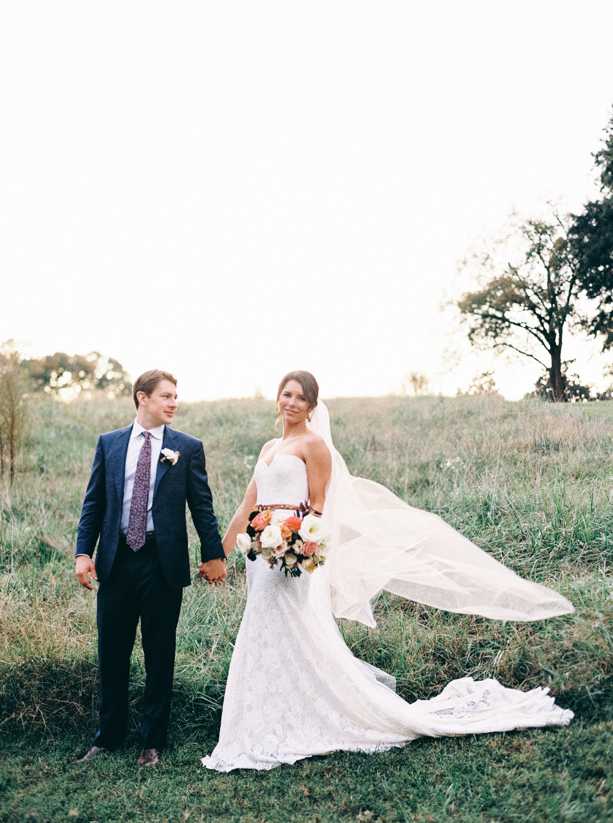 couple holding hands in field for wedding portrait