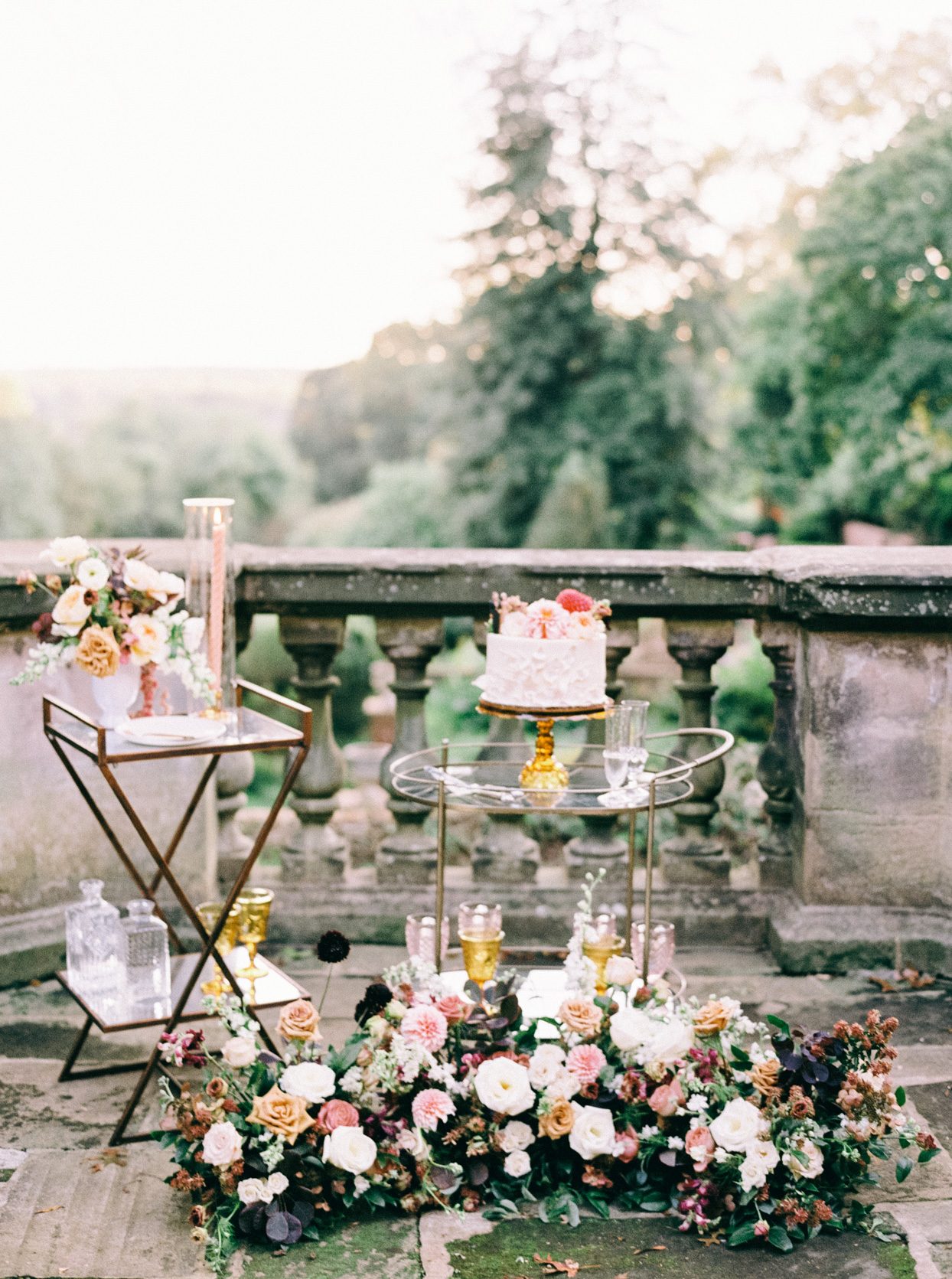 wedding cake on gold and glass cart sitting on balcony with flowers