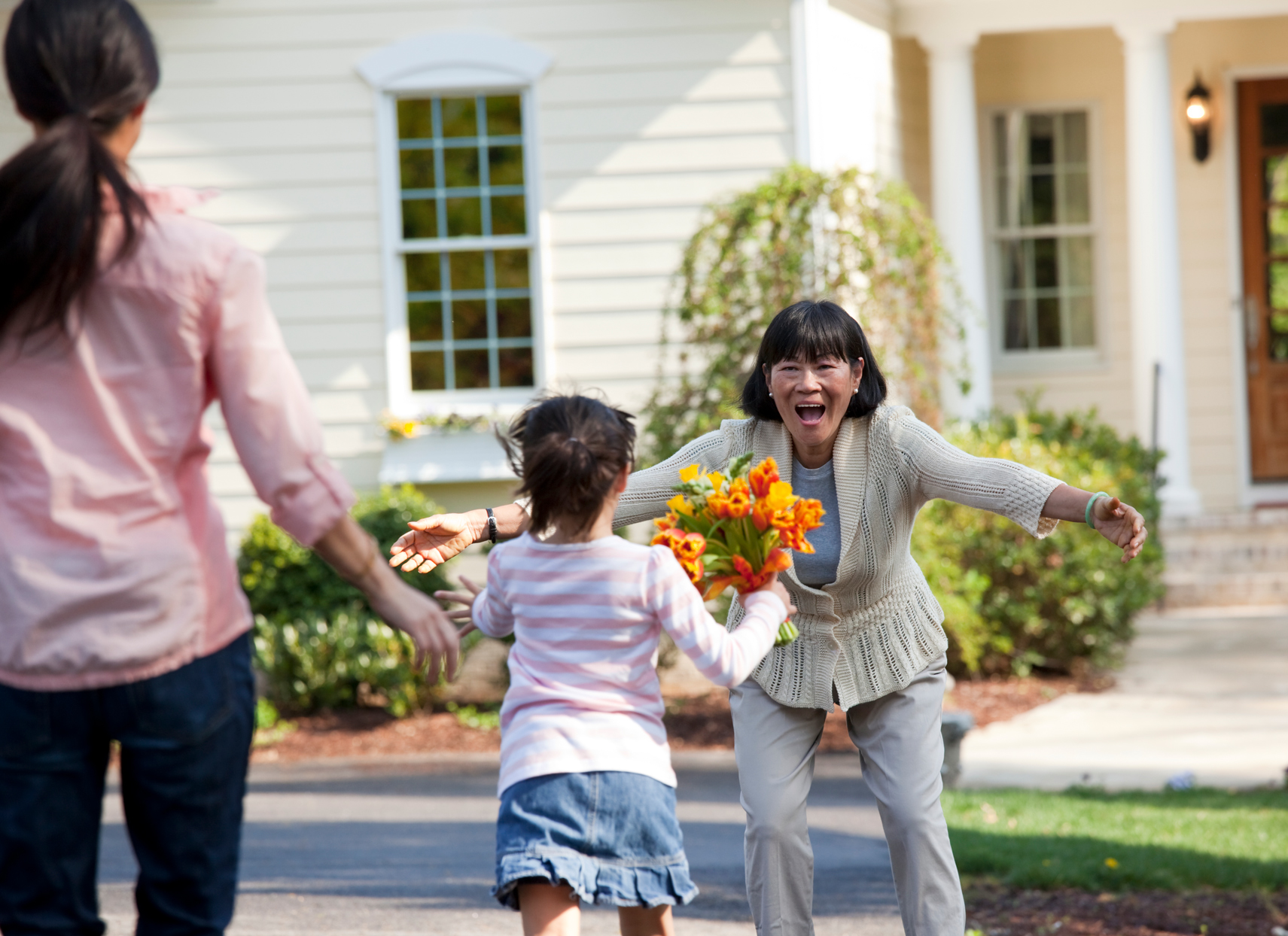 family welcoming woman with flowers